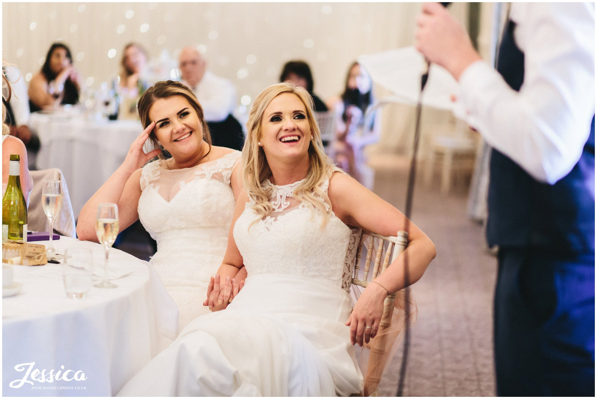 the couple laugh at an embarrassing story told by the best man