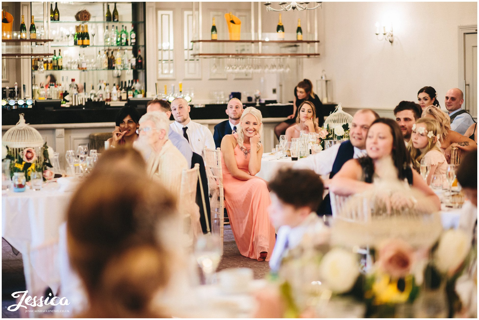 wedding guests laughing during the funny speeches