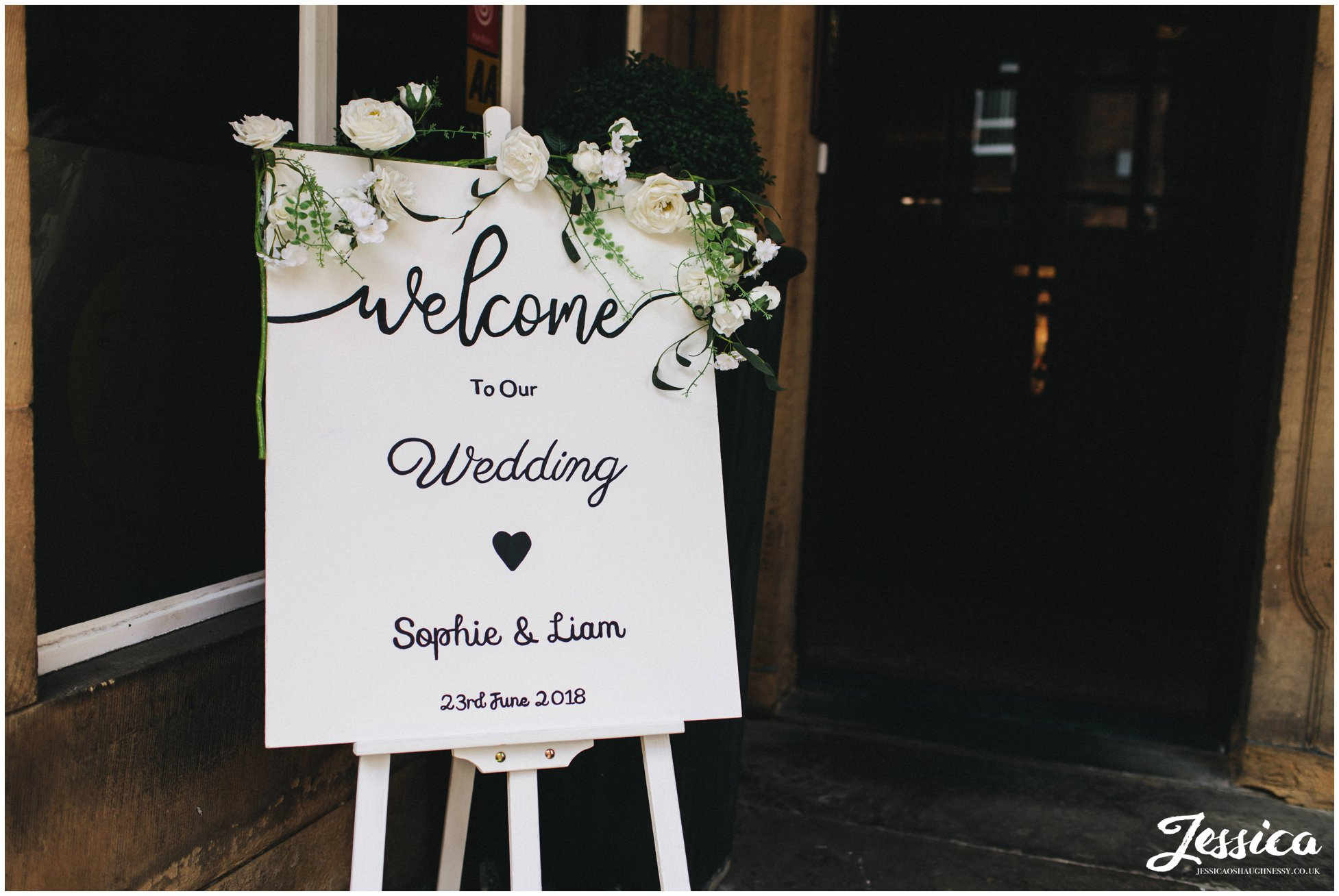 hand painted sign welcomes wedding guests into the venue