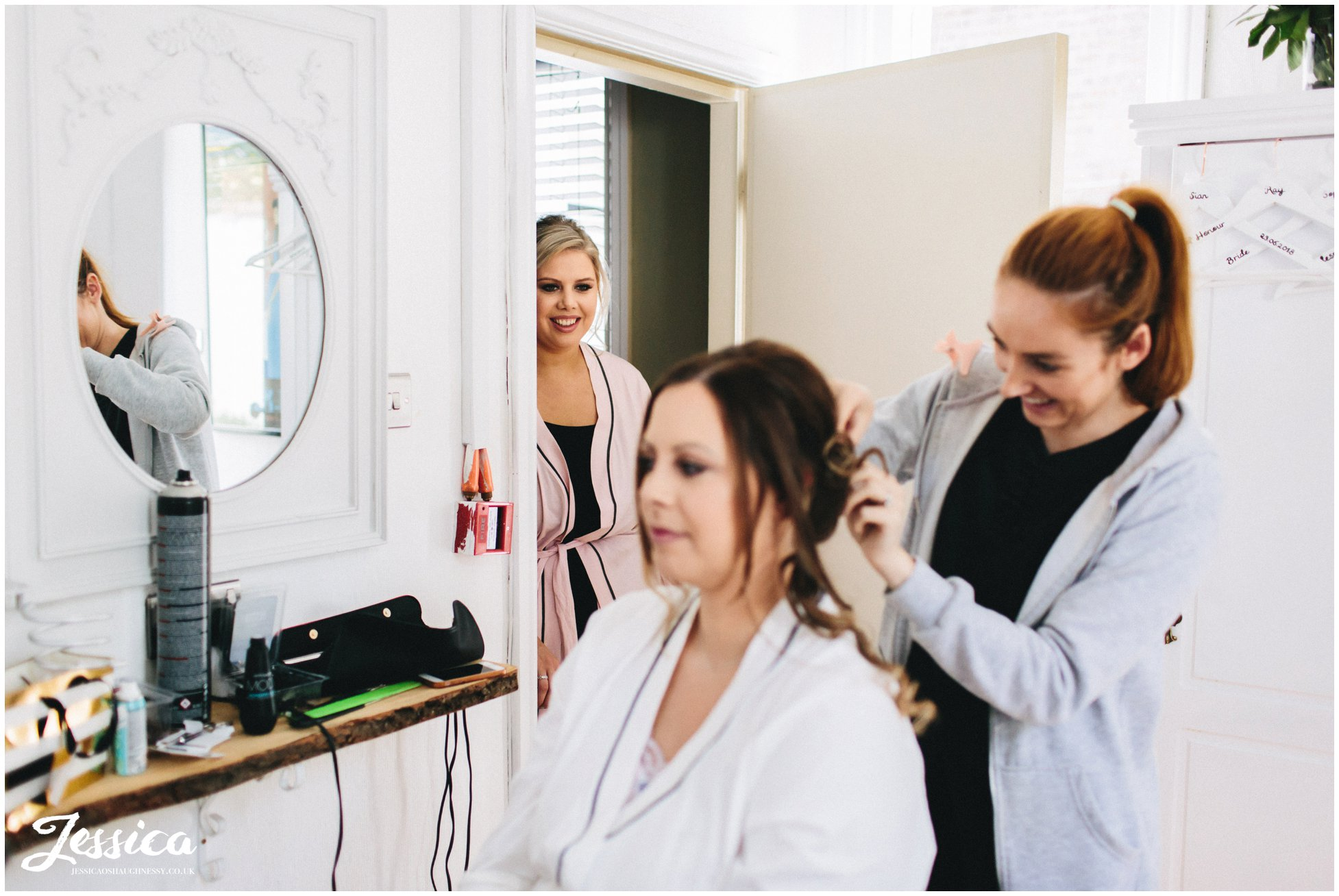 sister of the bride watches her having her make-up done for the ceremony