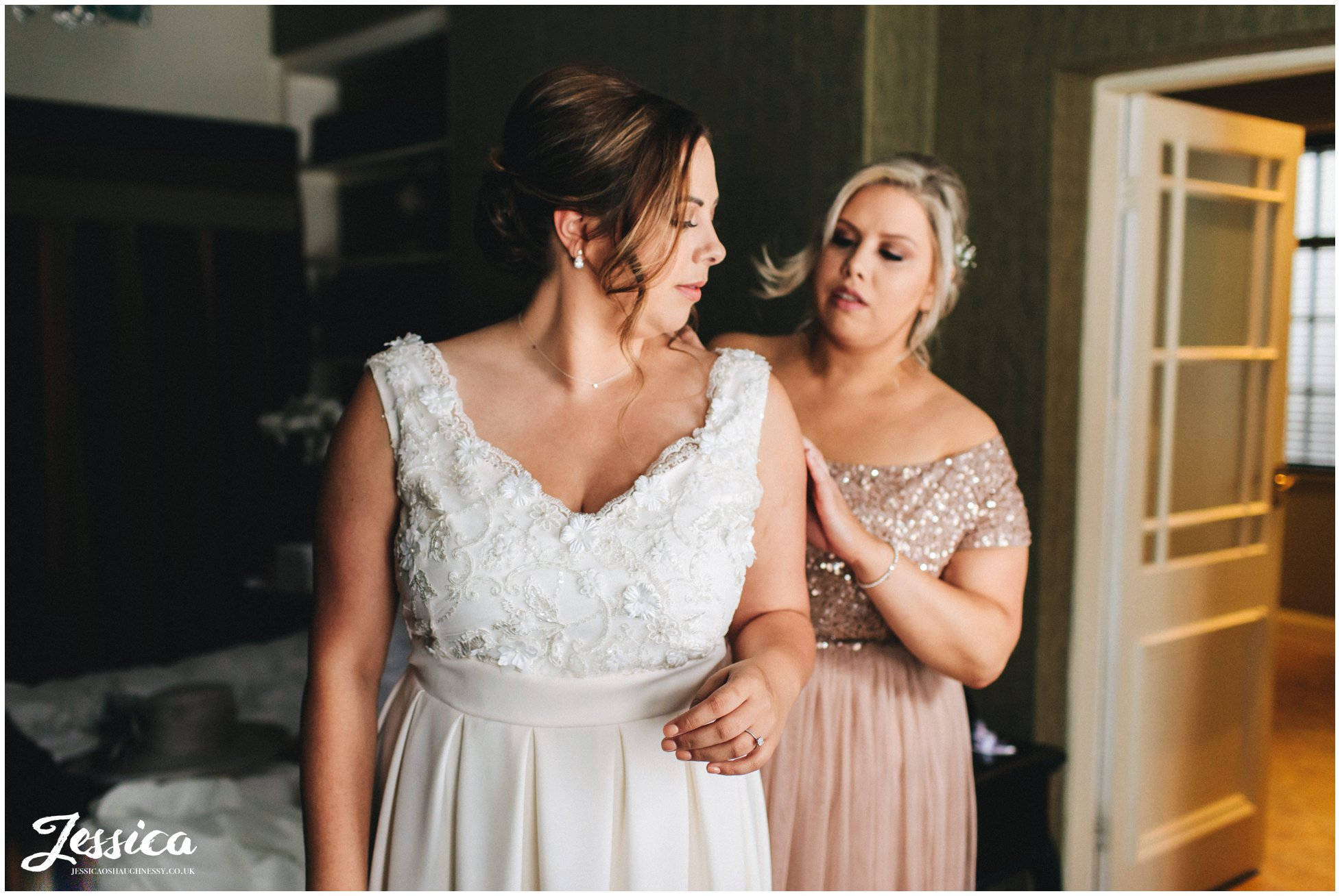 sister helps the bride into her wedding dress
