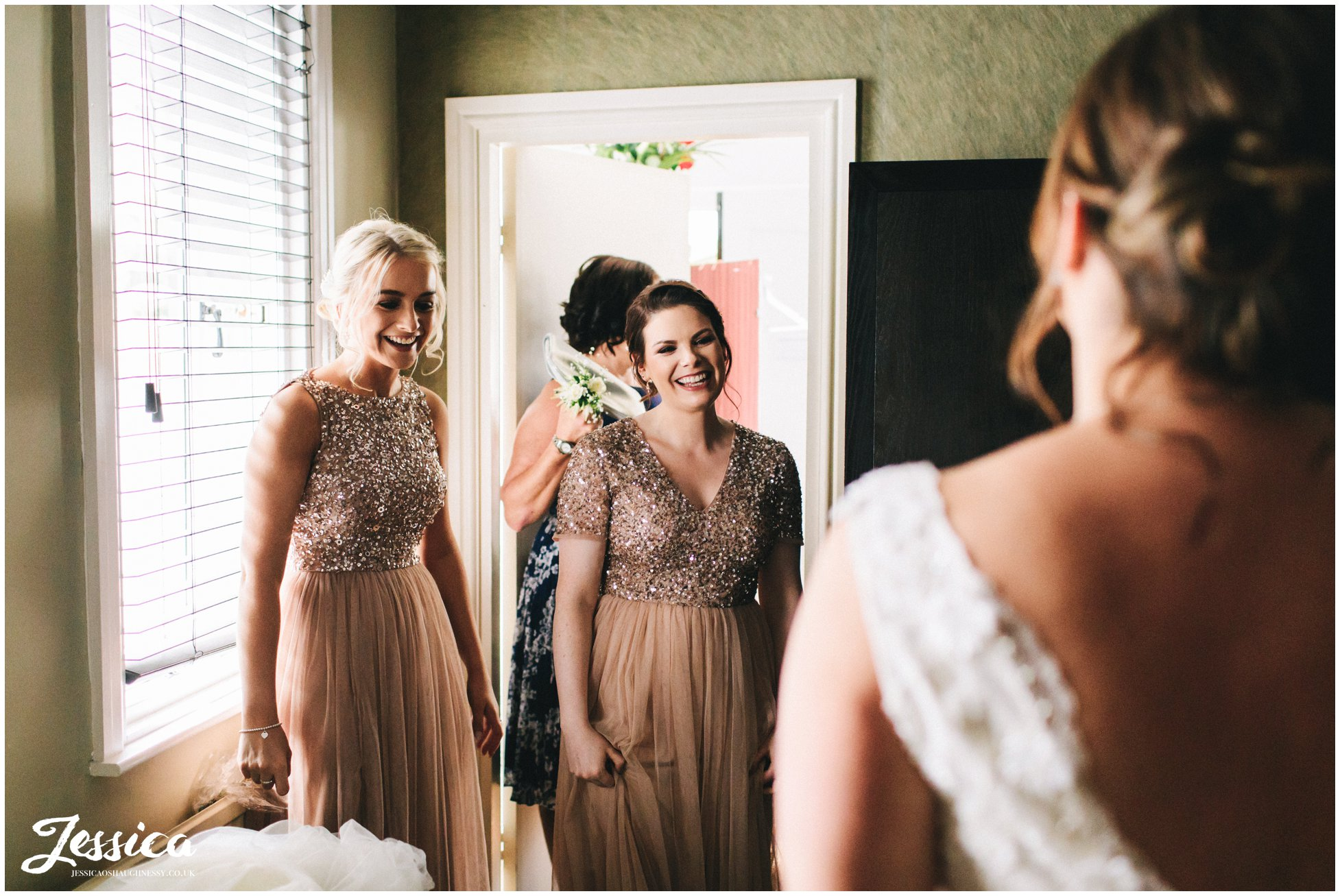 the bridesmaids look in awe after seeing the bride in her dress