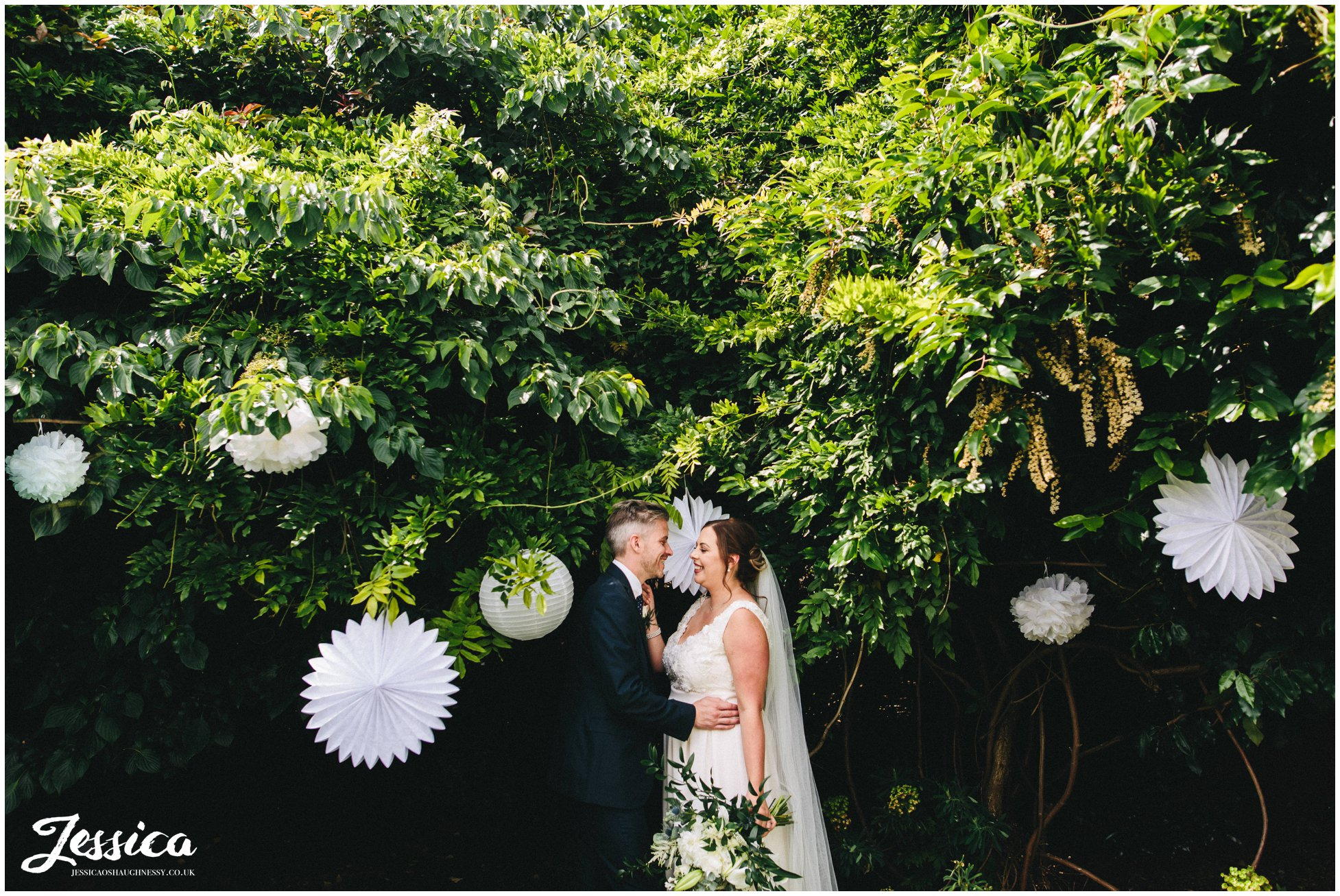 the couple kiss in front of the gardens decorated with paper lanterns