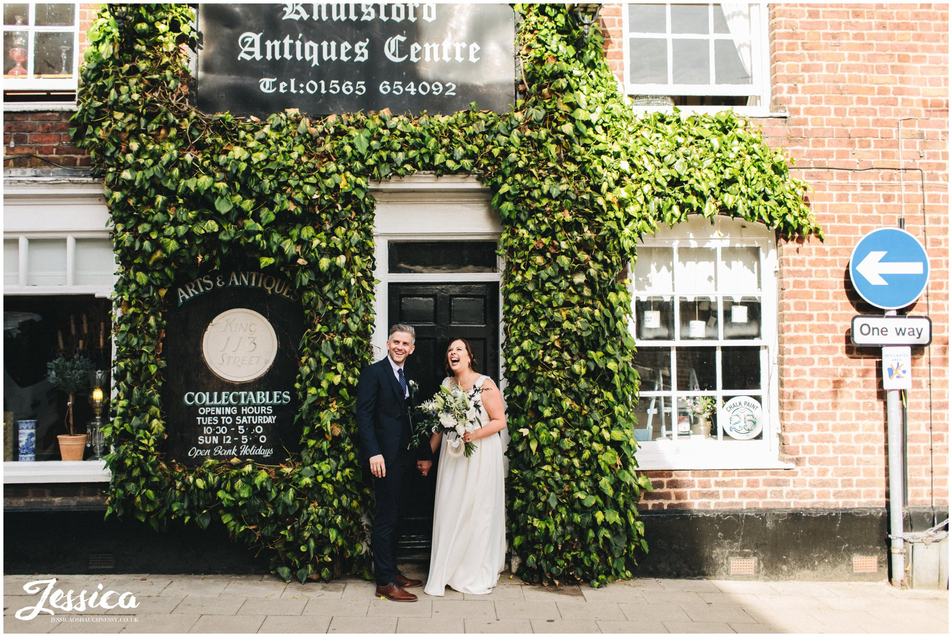 the couple laugh standing in a quirky doorway on knutsford high street