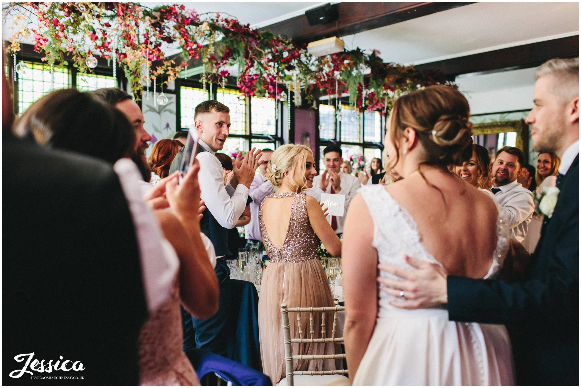 guests applaud as the couple enter the garden room at belle epoque