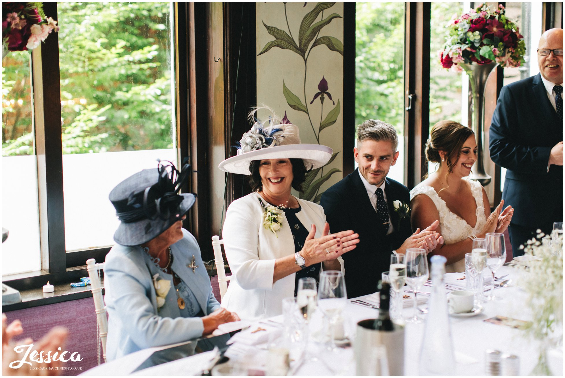 the top table applaud the father of the bride as he finishes his speech