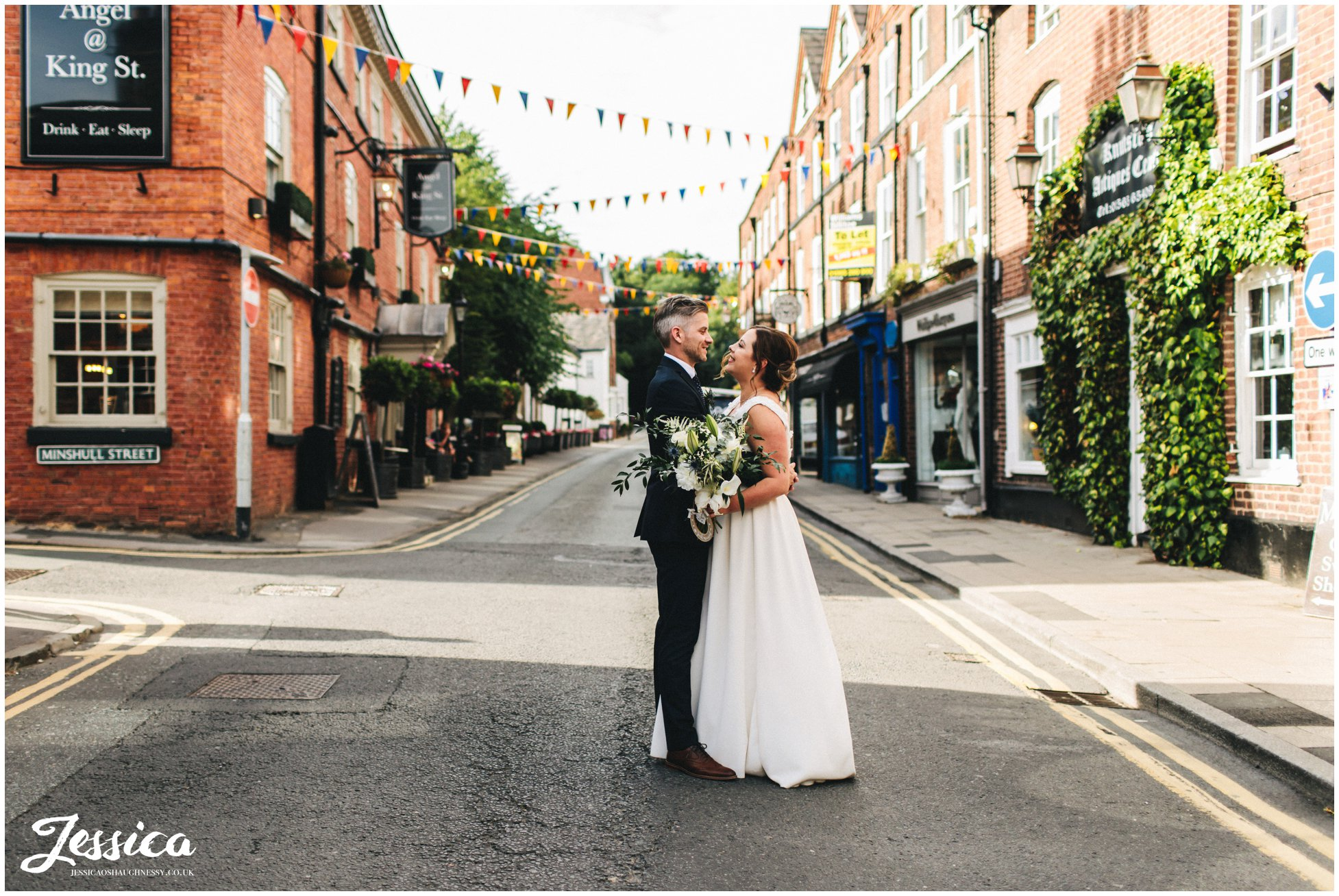 the newly wed's kiss in the middle of the road decorated with bunting