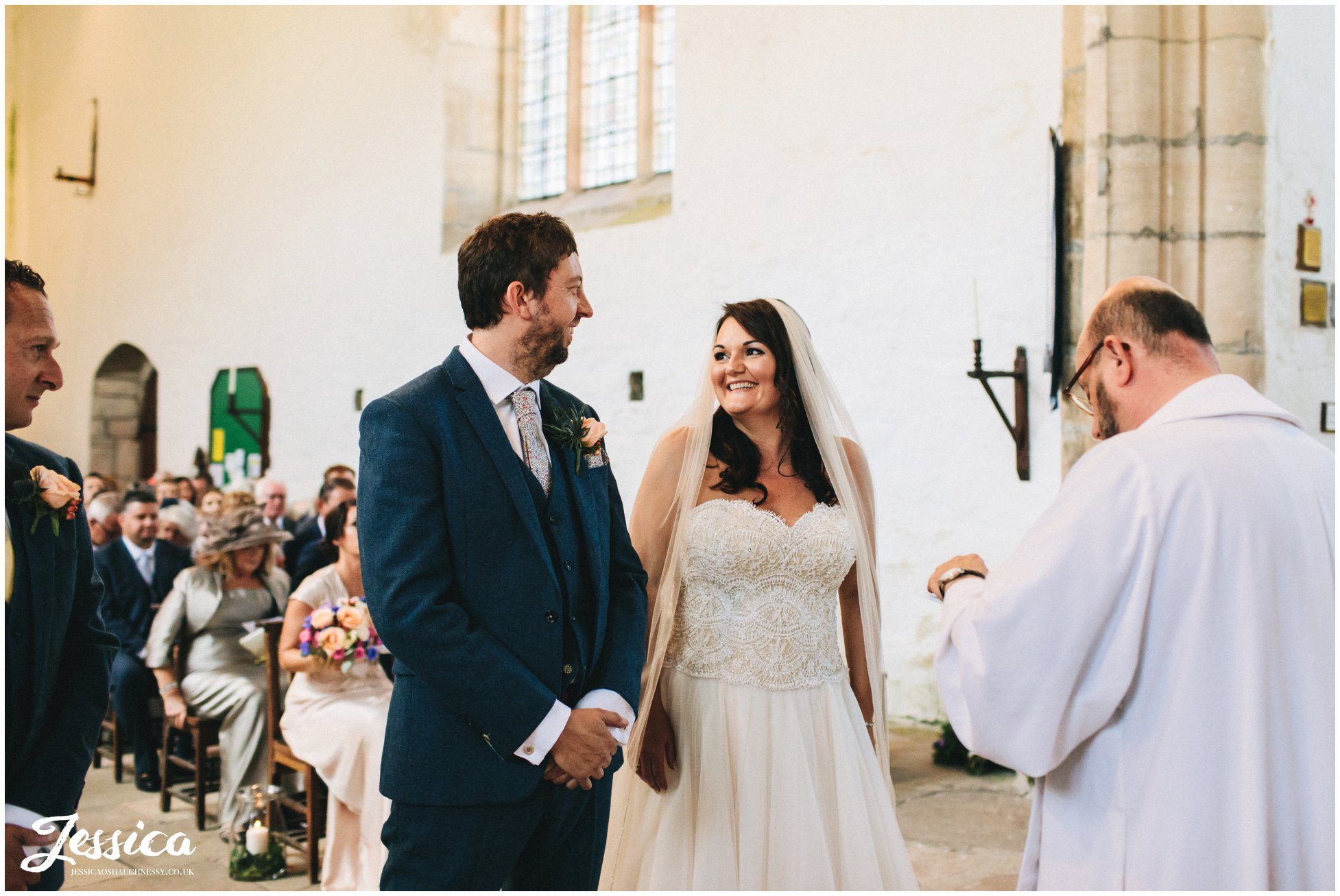 the bride smiles at her husband to be during the service