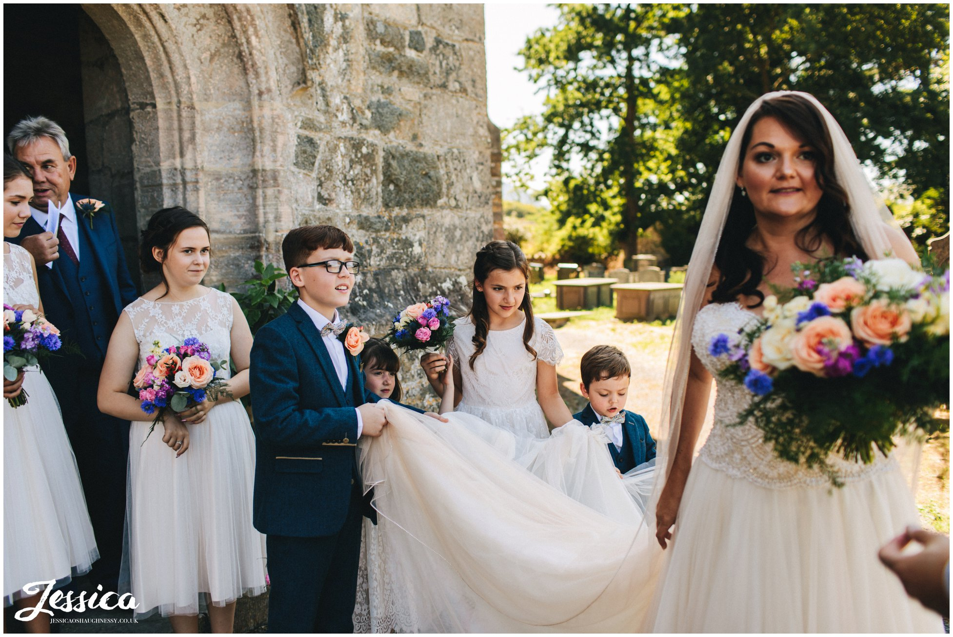 children help the bride by carrying her train
