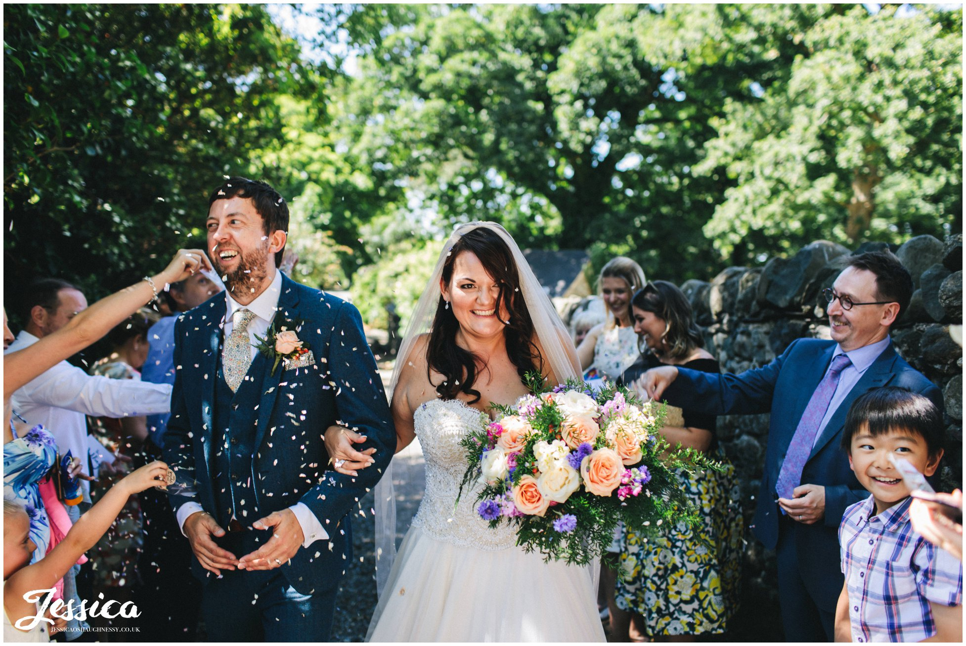 the newly wed's get showered with confetti after their wedding ceremony