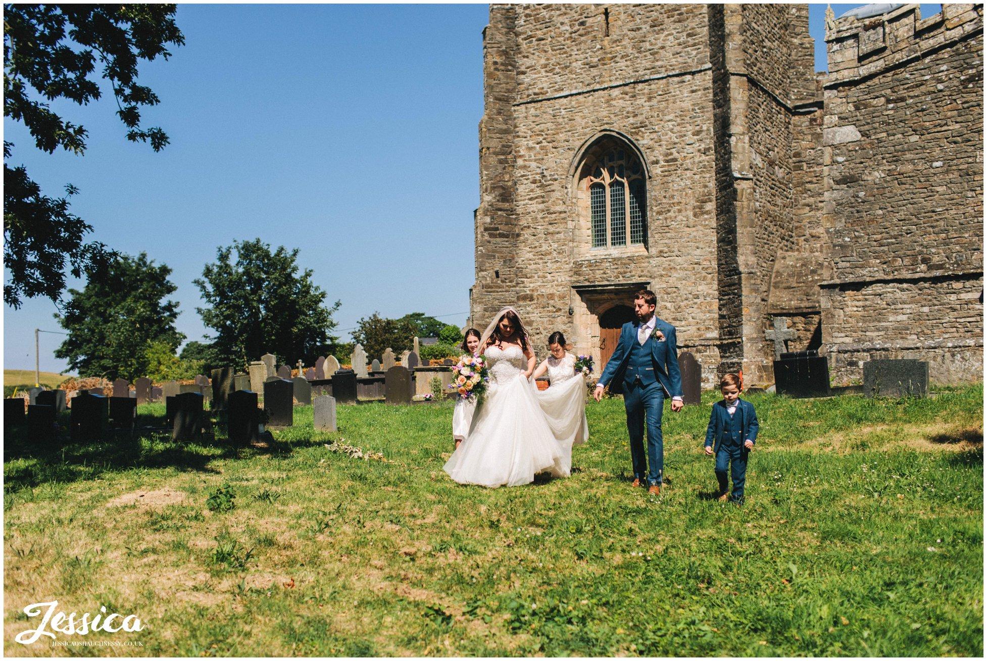 the new couple walk through the church grounds at st beuno's church in Caernarfon