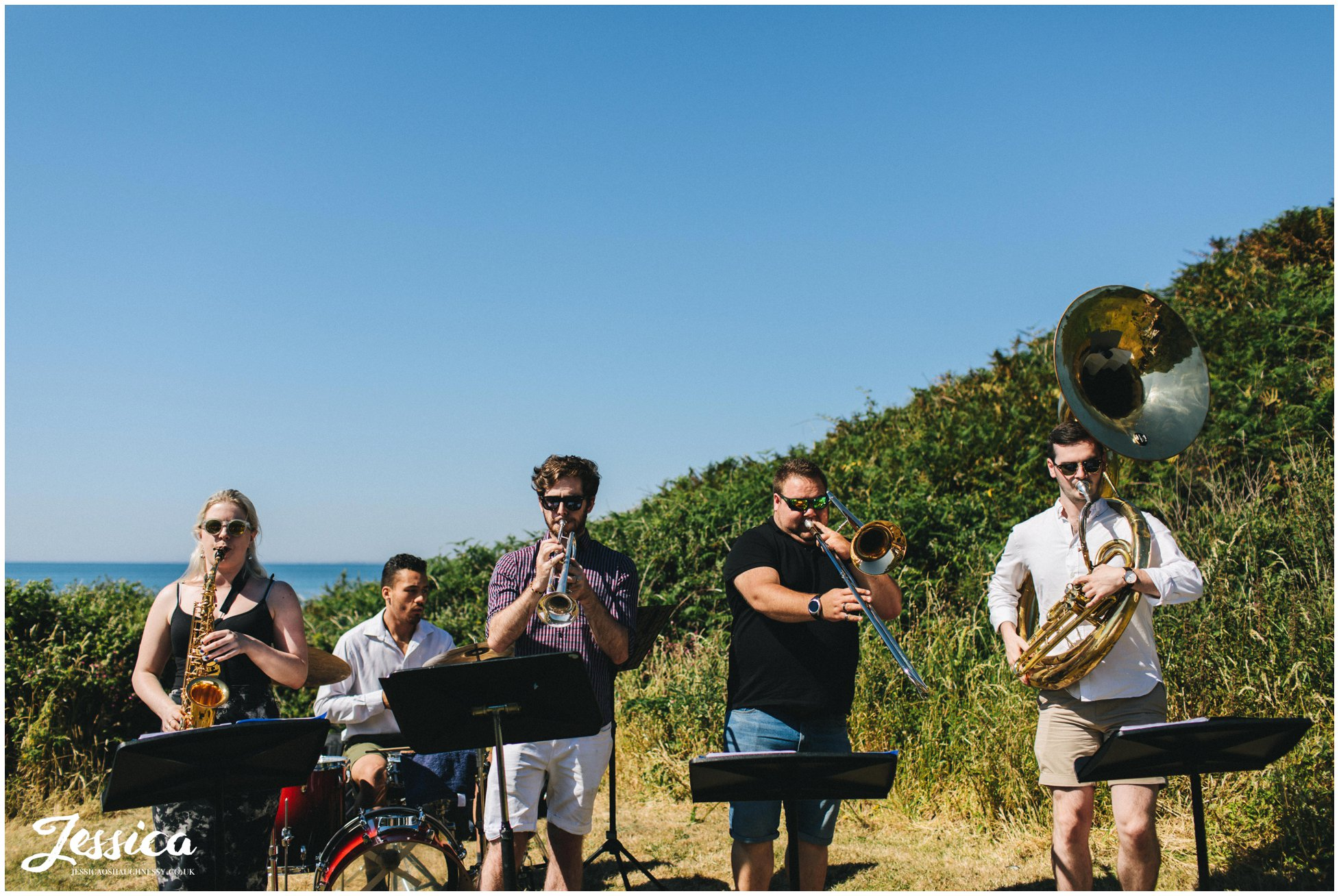 a brass band plays to the wedding party at bach wen farm in north wales