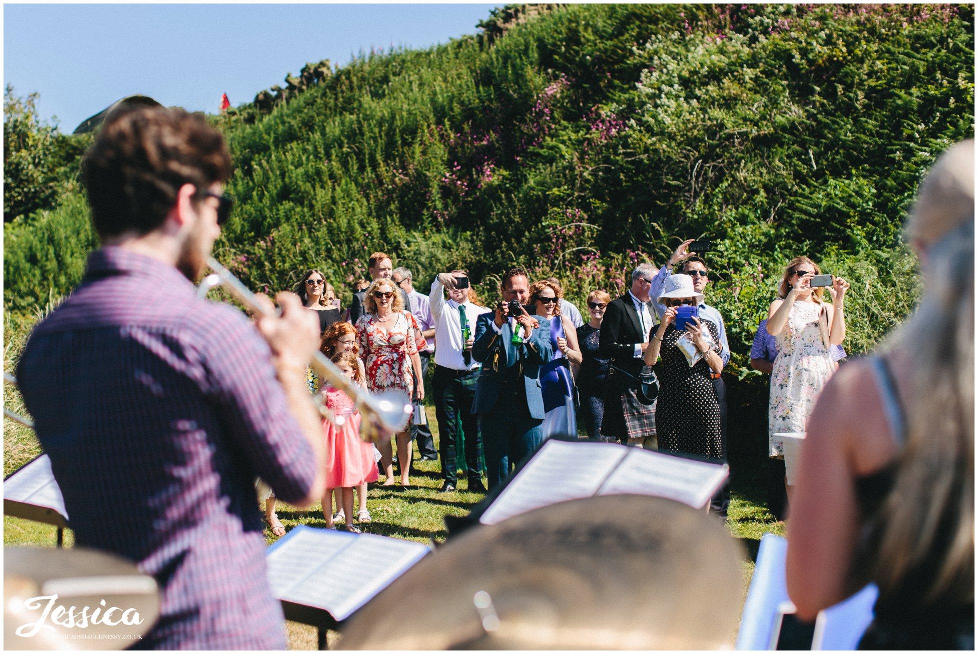 wedding guests enjoy the brass band playing by Caernarfon bay