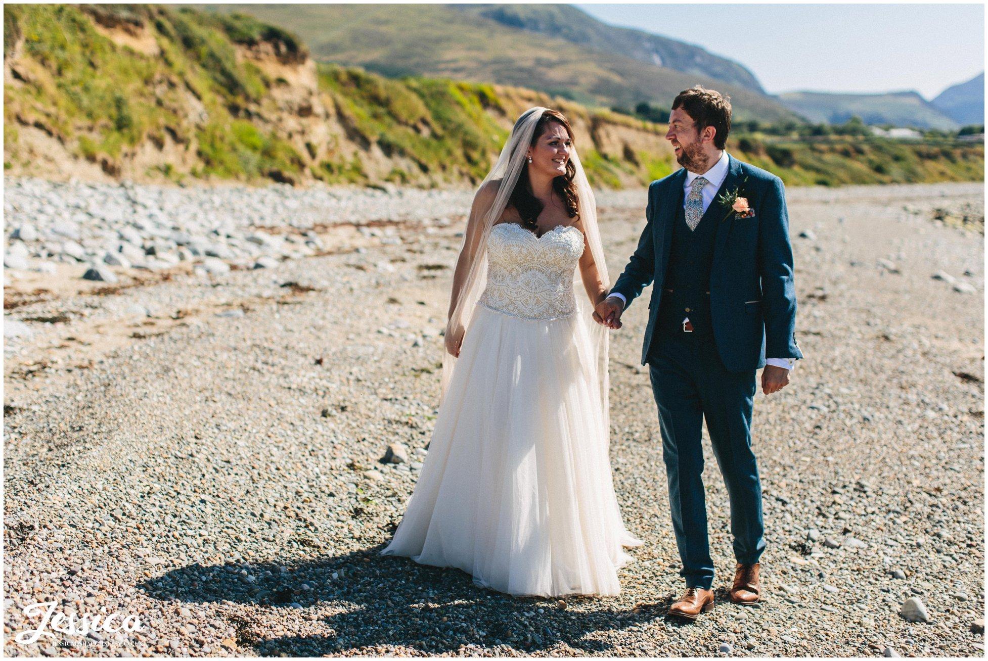 newly wed's walk hand in hand down Caernarfon bay beach