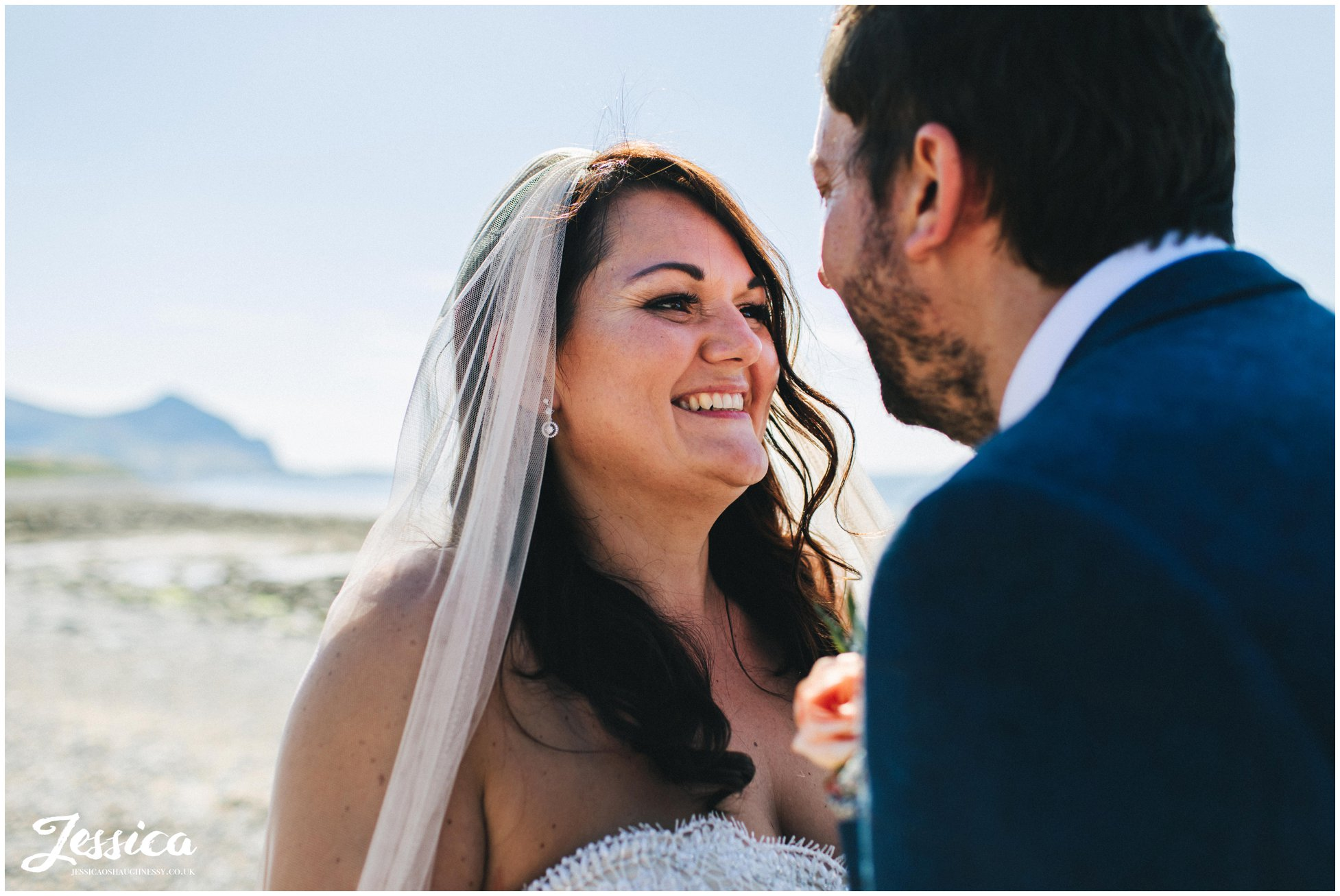 the bride smiles to her groom with the sea behind them