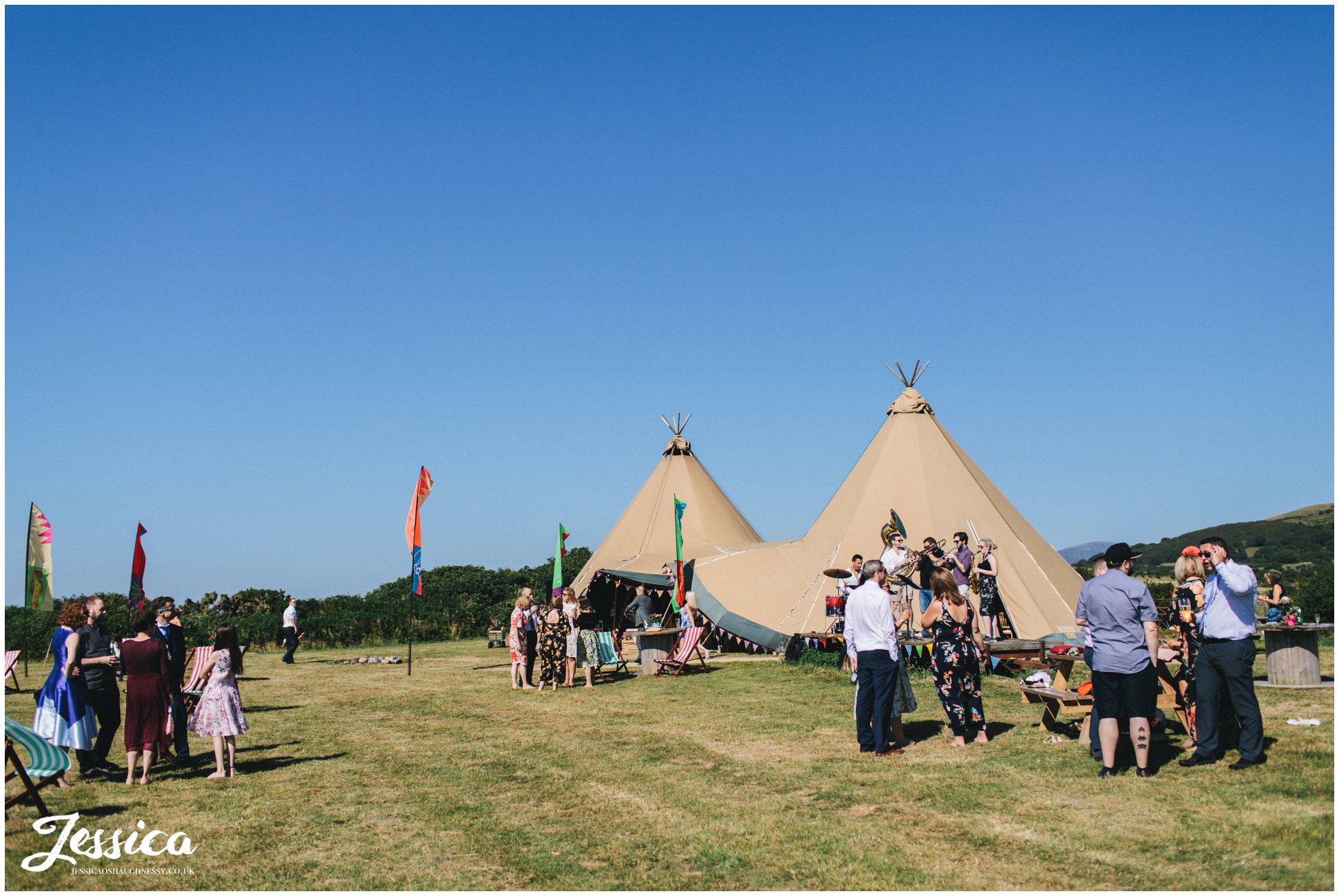 wedding guest stand outside with tipi in the background