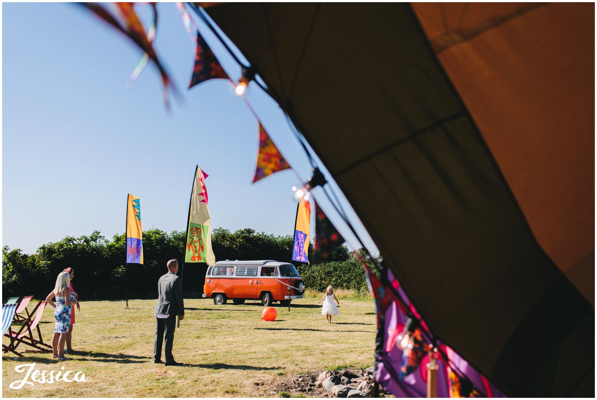 vw camper is parked on the field with the tipi