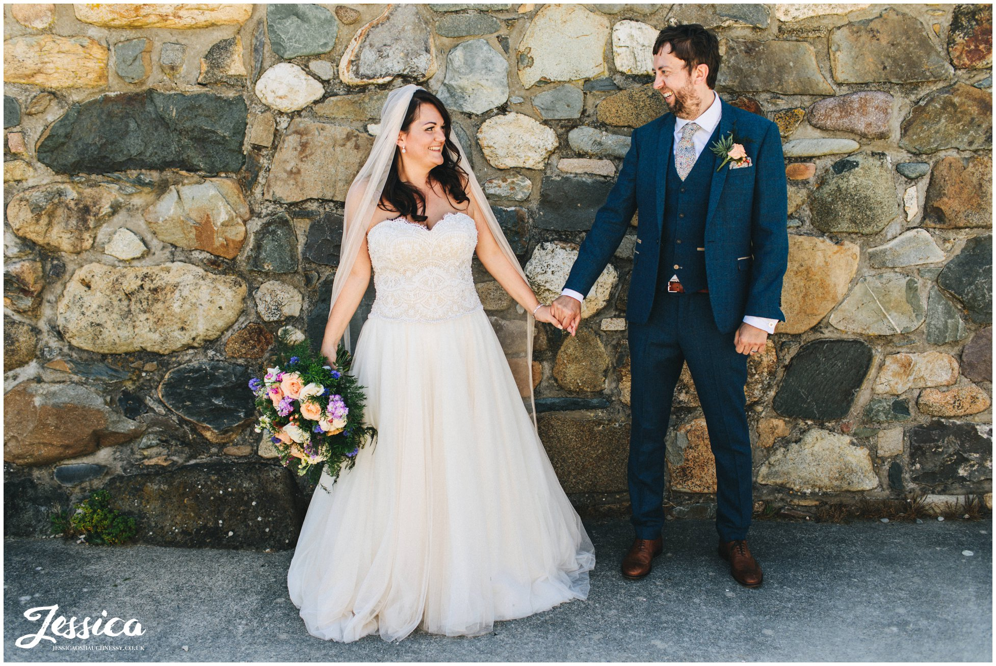 newly wed's stand in front of welsh stone wall