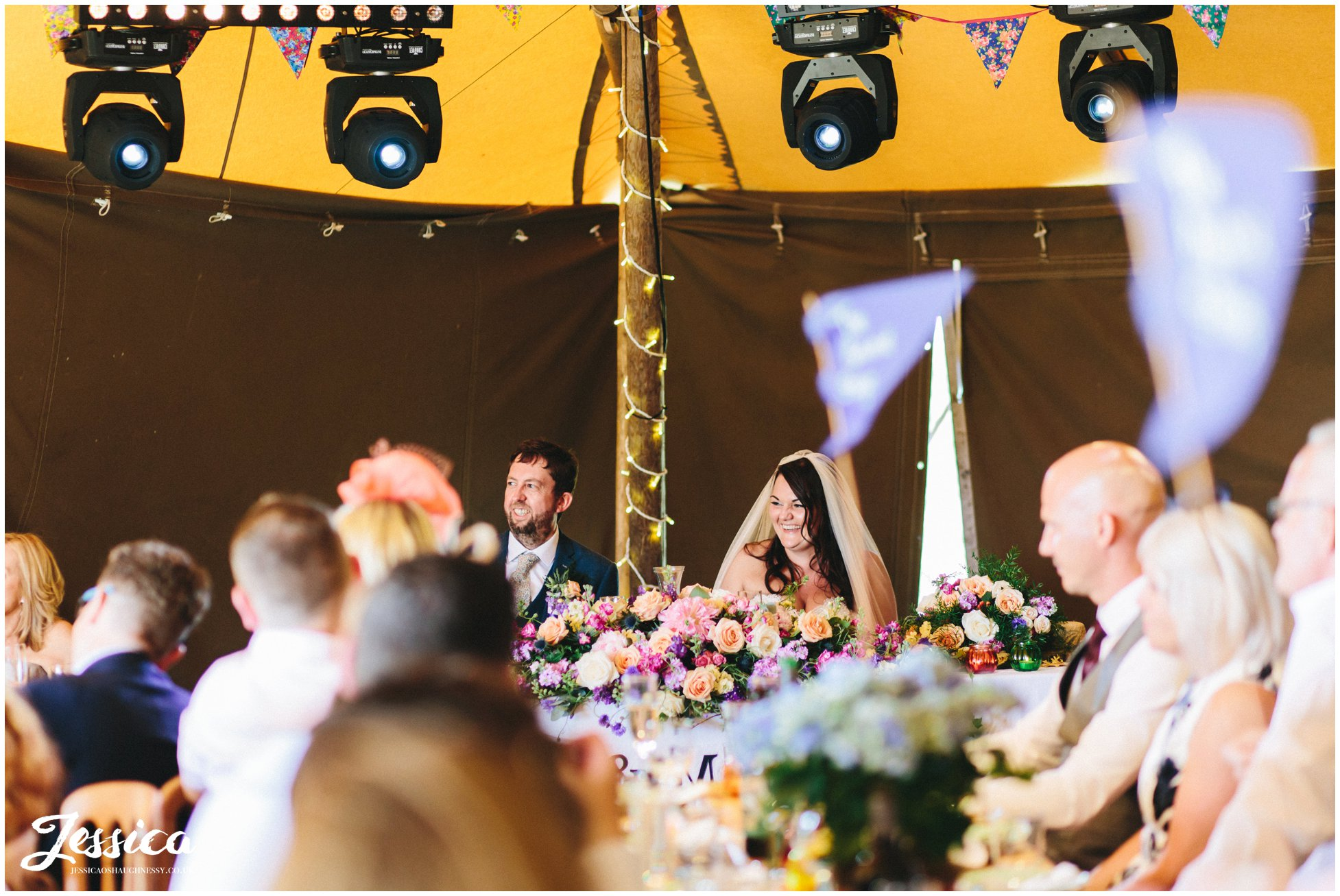 the bride & groom smile as the best man gives his speech at bach wen farm