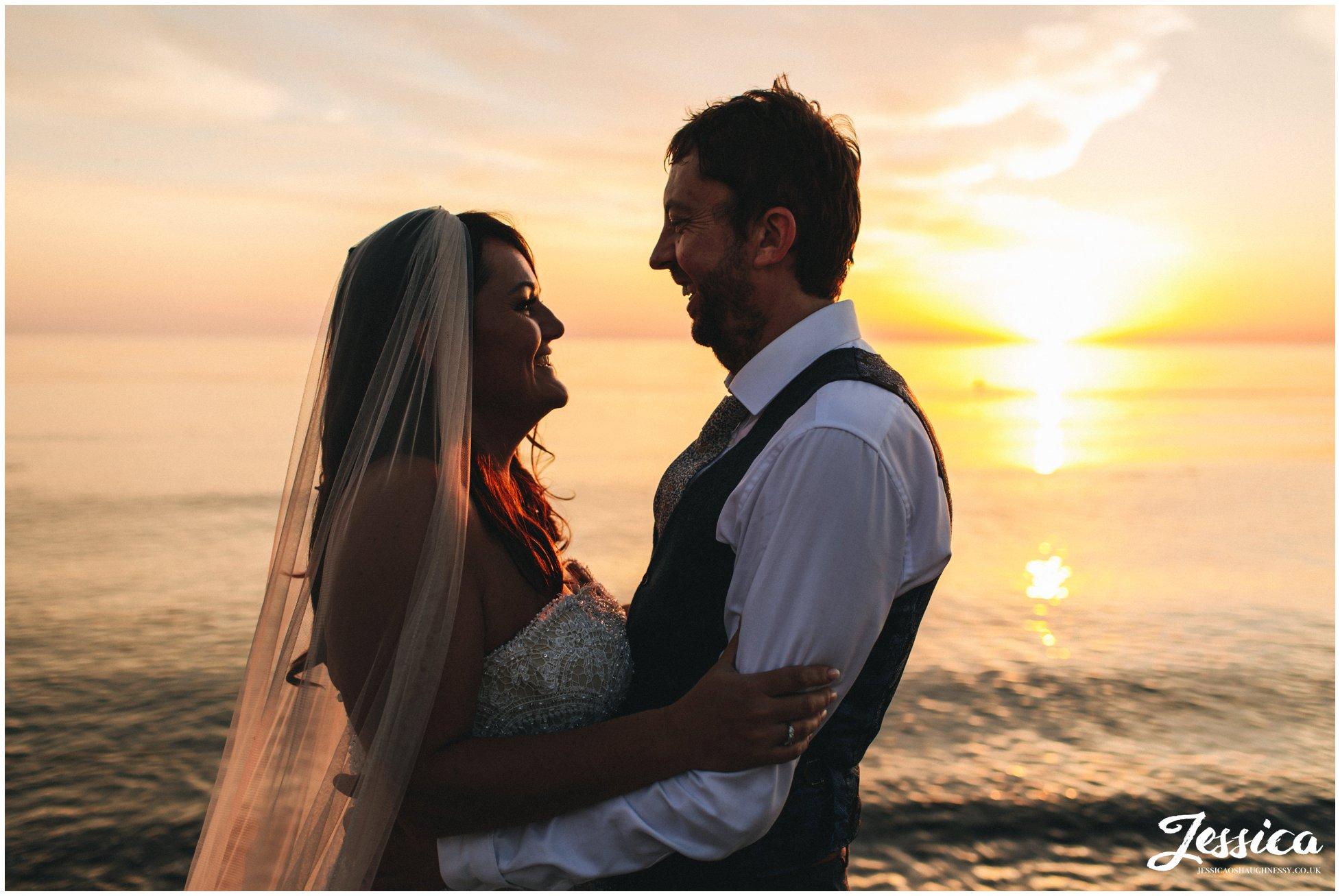 couple smile at each other as the sun sets on Caernarfon bay