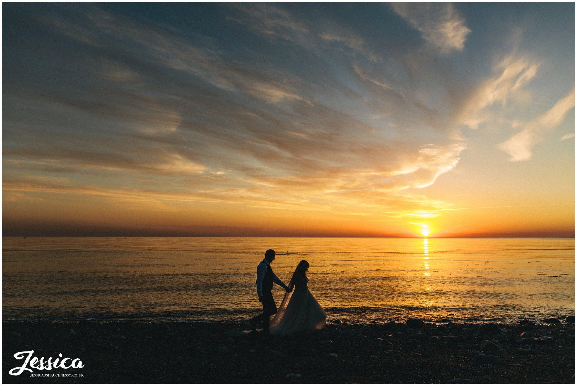 newly wed's walk along Caernarfon bay in the sunset at bach wen farm
