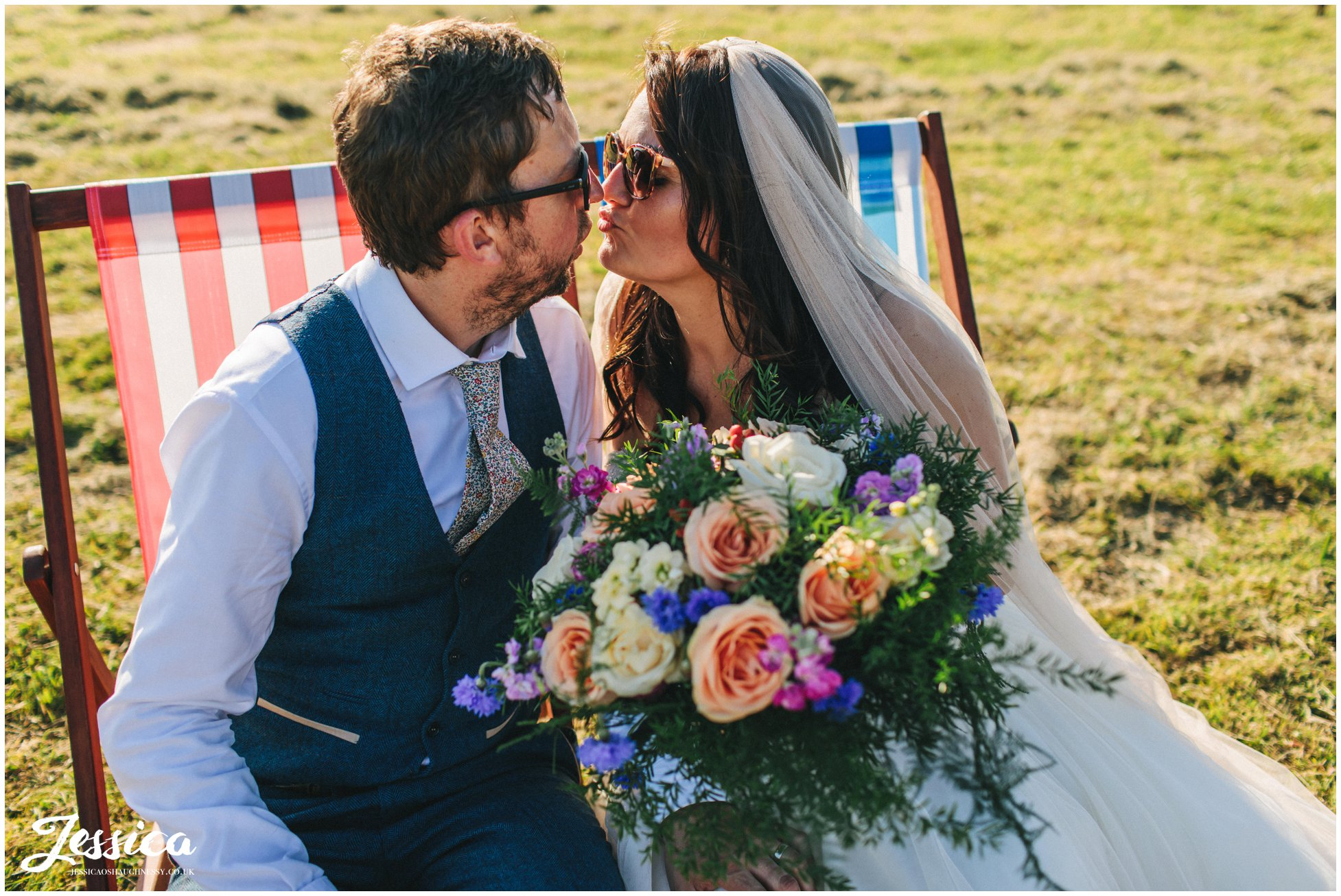 bride & groom pose on the deck chairs with sunglasses on