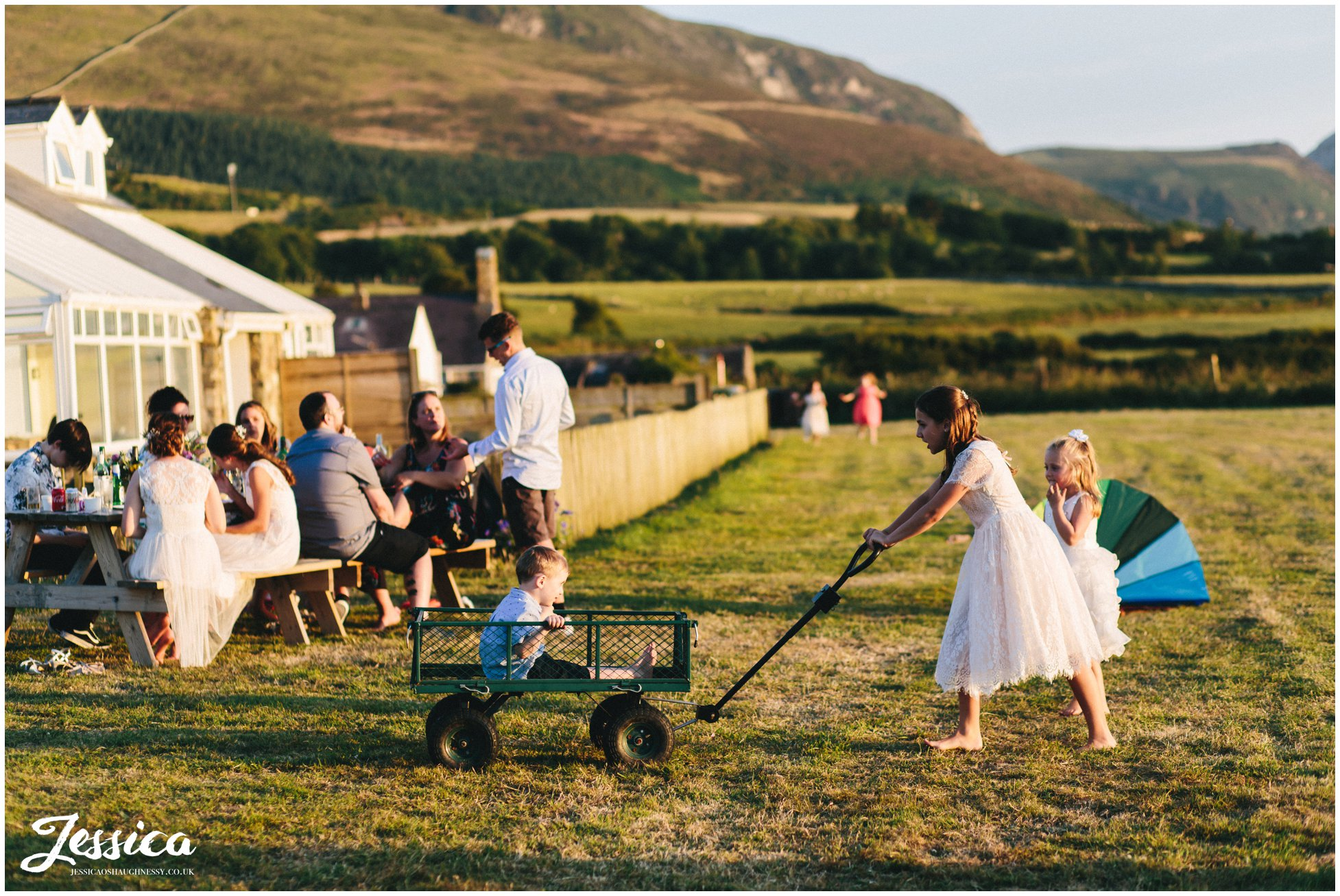bridesmaid drags young child around in a trailer