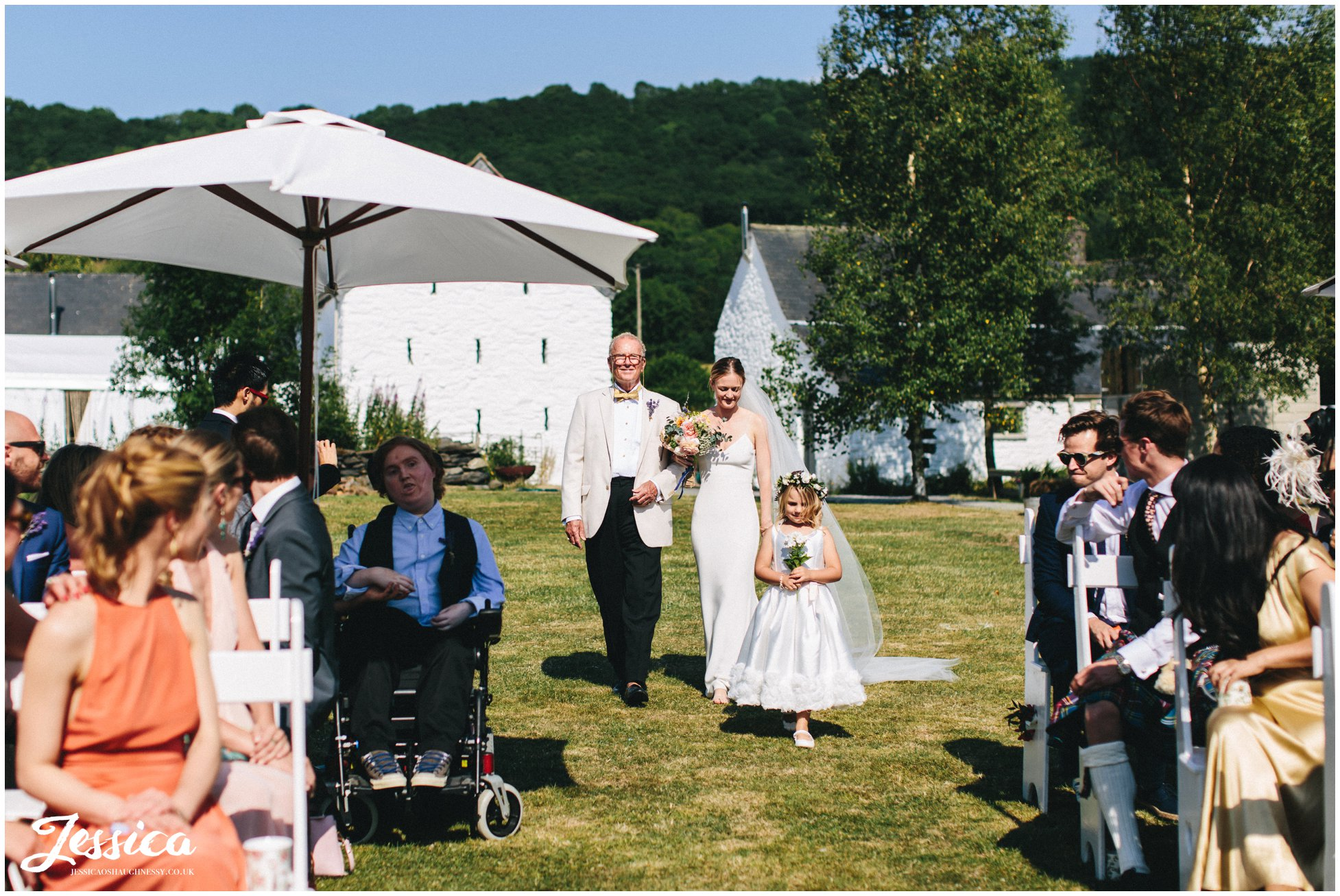 the bride walks with her father down the aisle