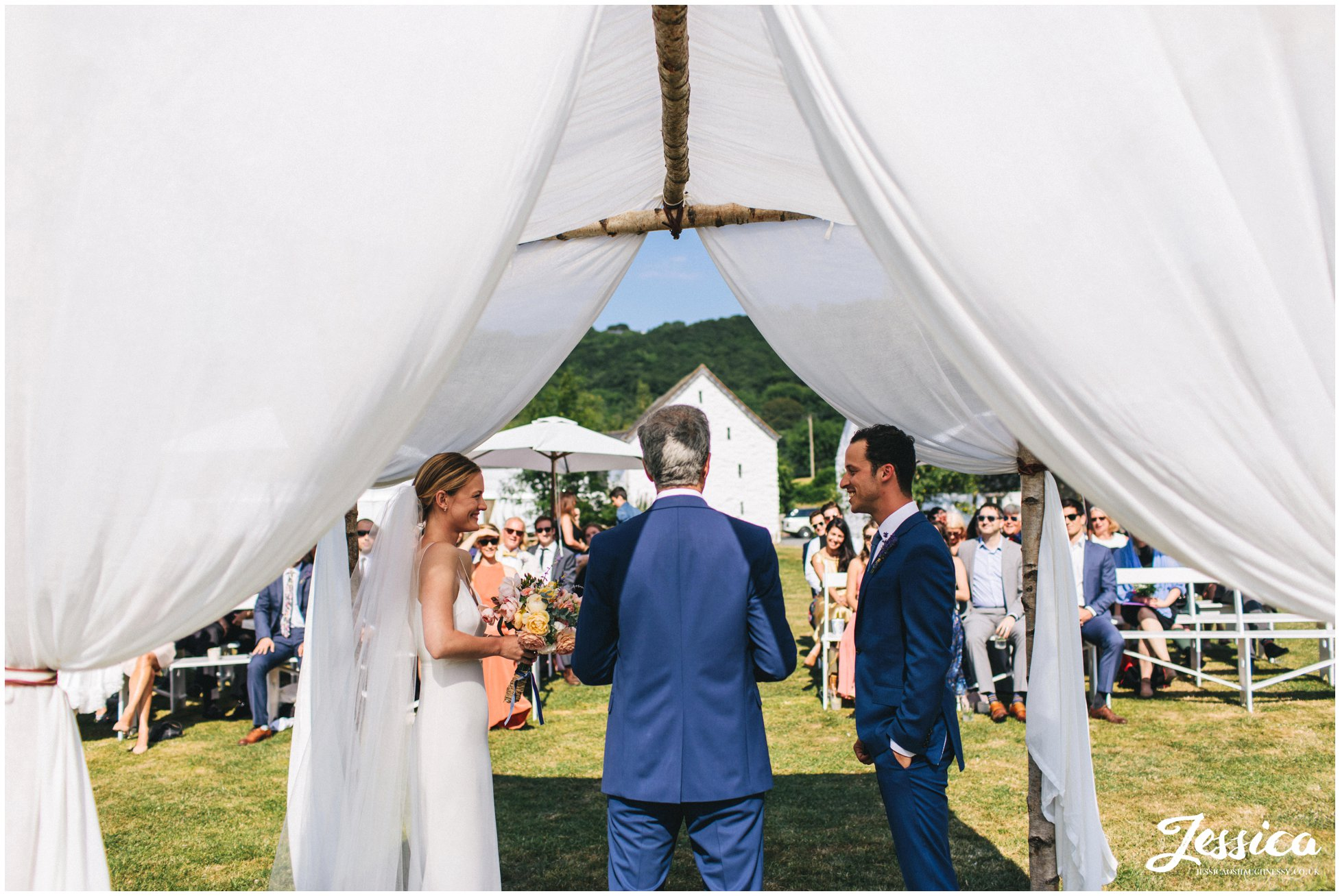 the couple have their wedding ceremony under the chuppah