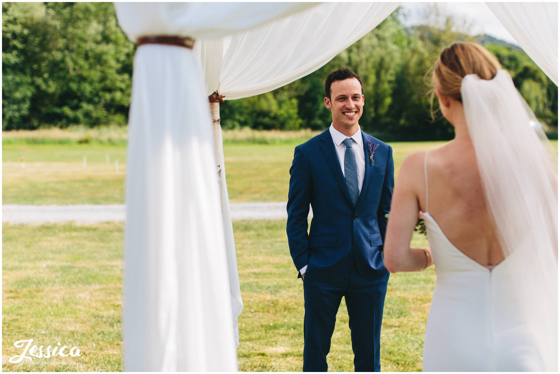 the groom admires his bride at hafod farm during the wedding ceremony
