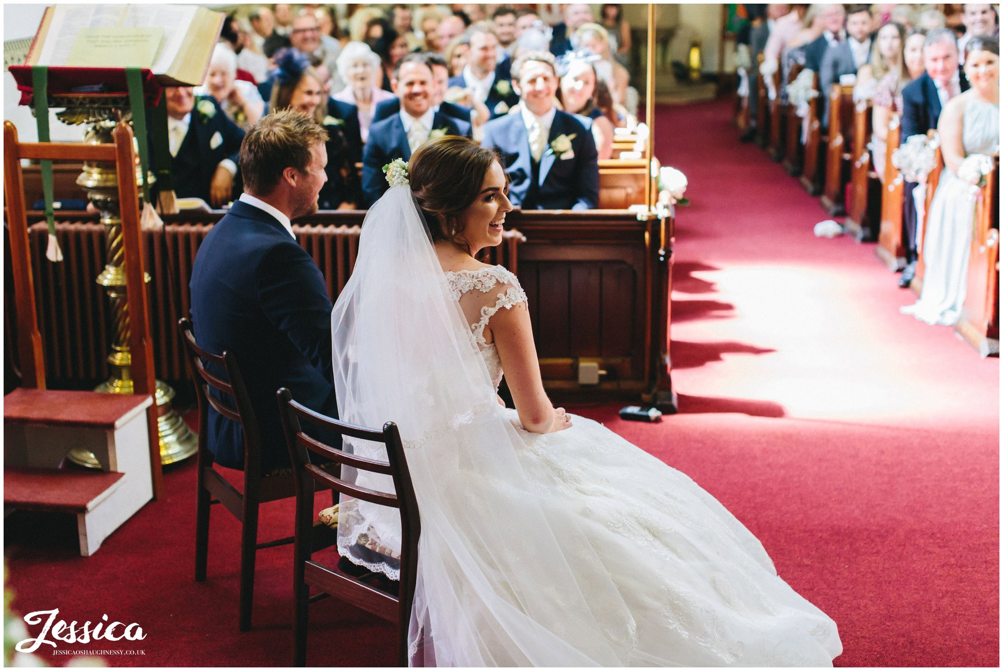 bride smiles as the reverend gives his sermon