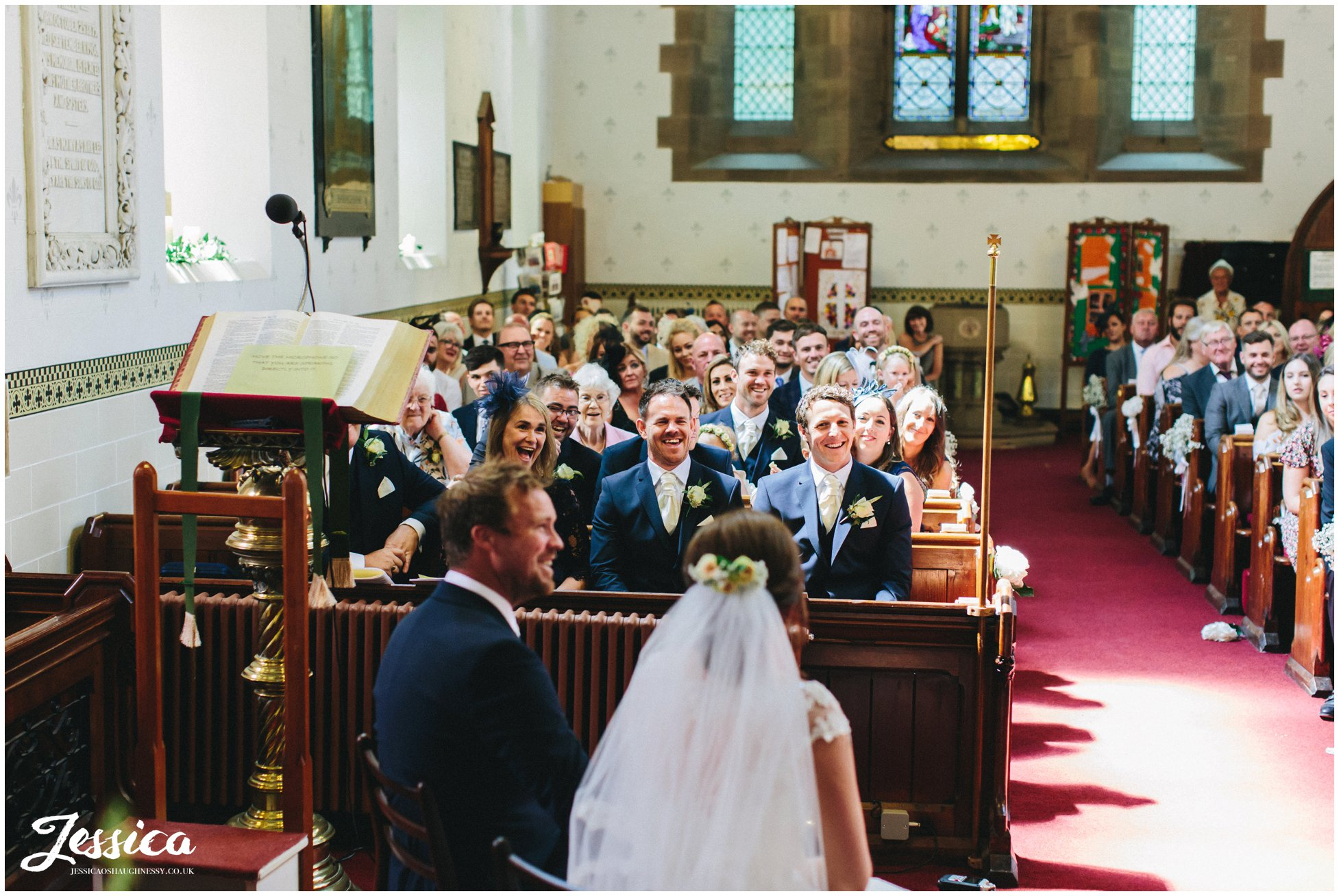 guests laugh during the wedding ceremony at st annes church in singleton
