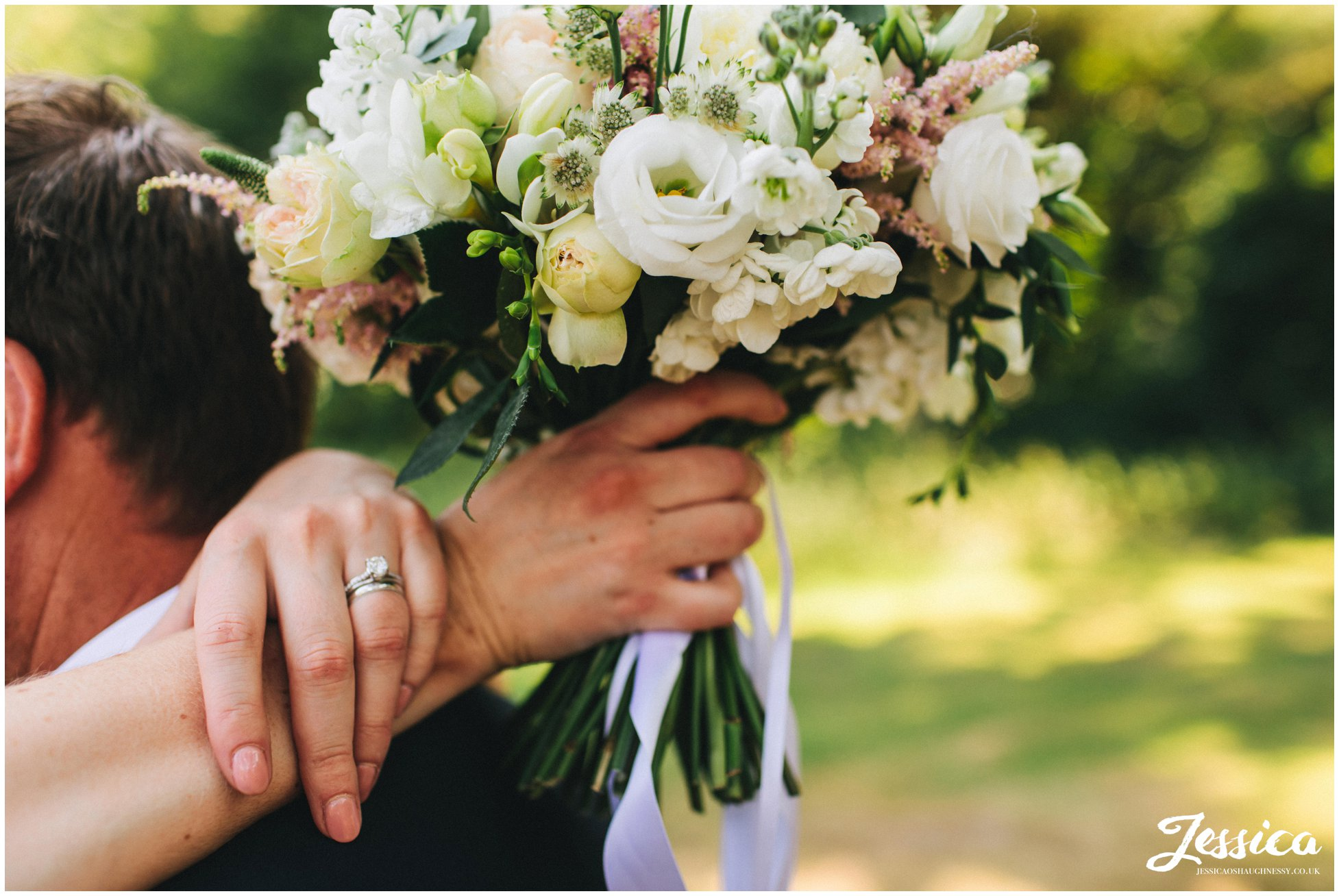 bride shows off her wedding rings and bride bouquet