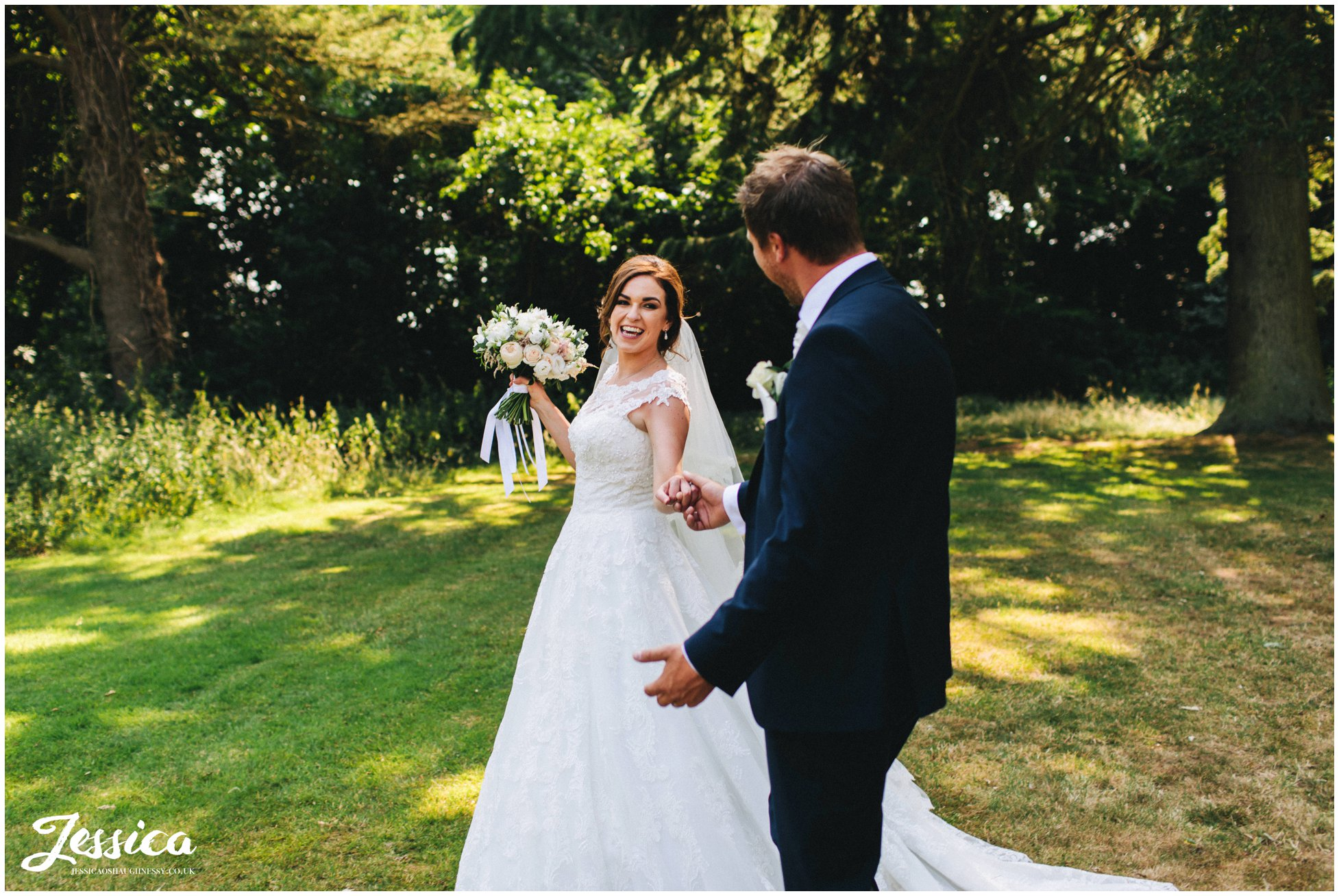 bride laughs at her groom as they walk through bartle hall's grounds