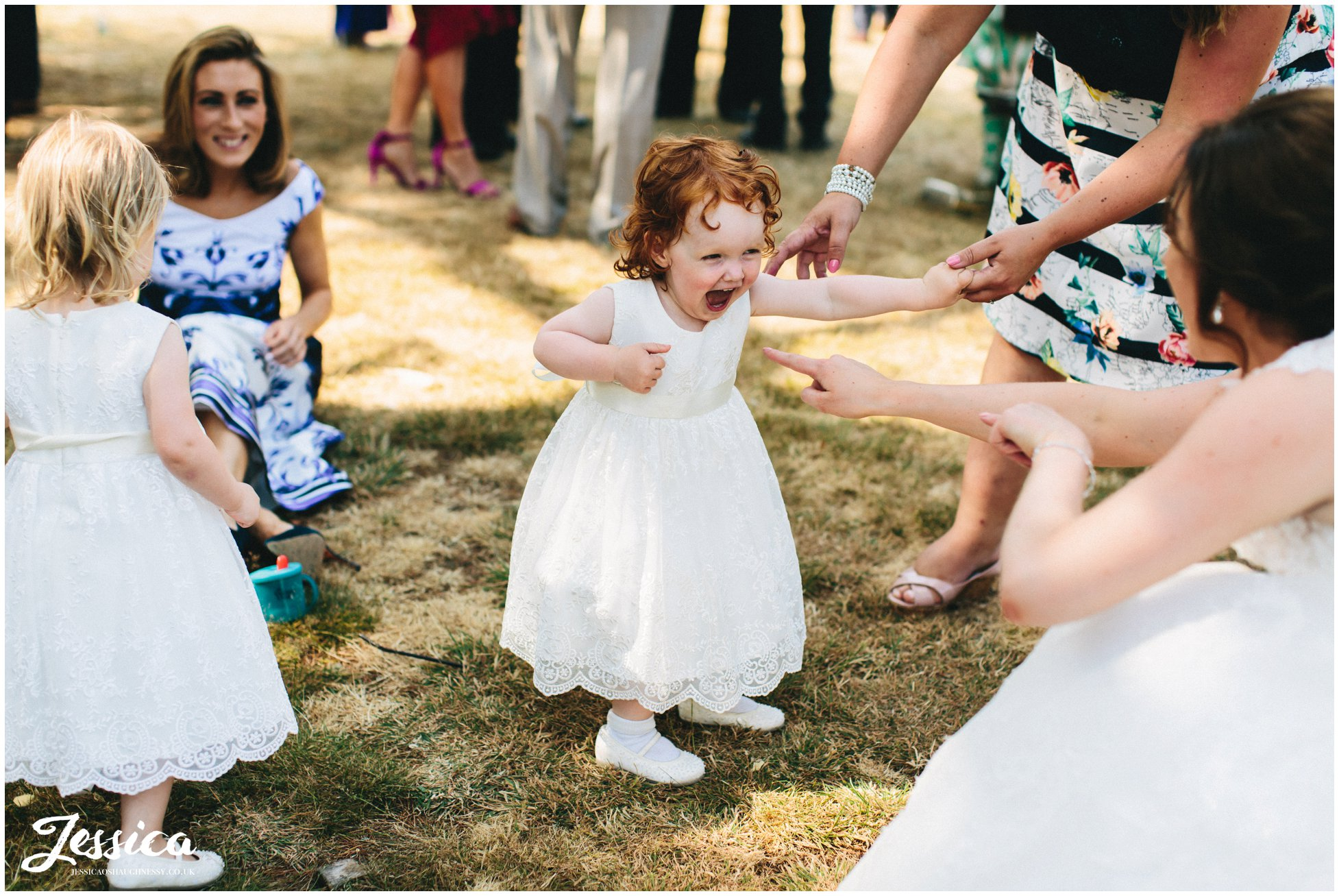 a flower girl laughs as the bride plays with her