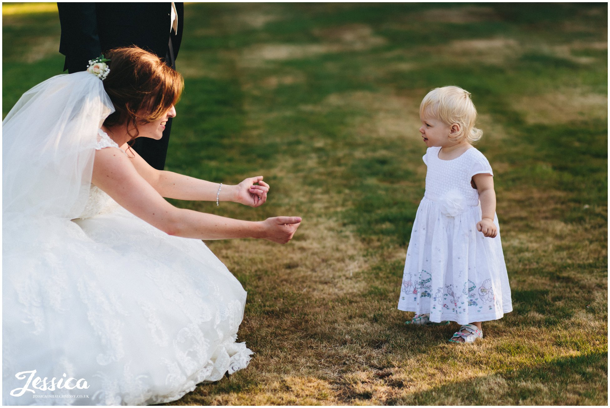 bride puts her arms out to hug the flower girl