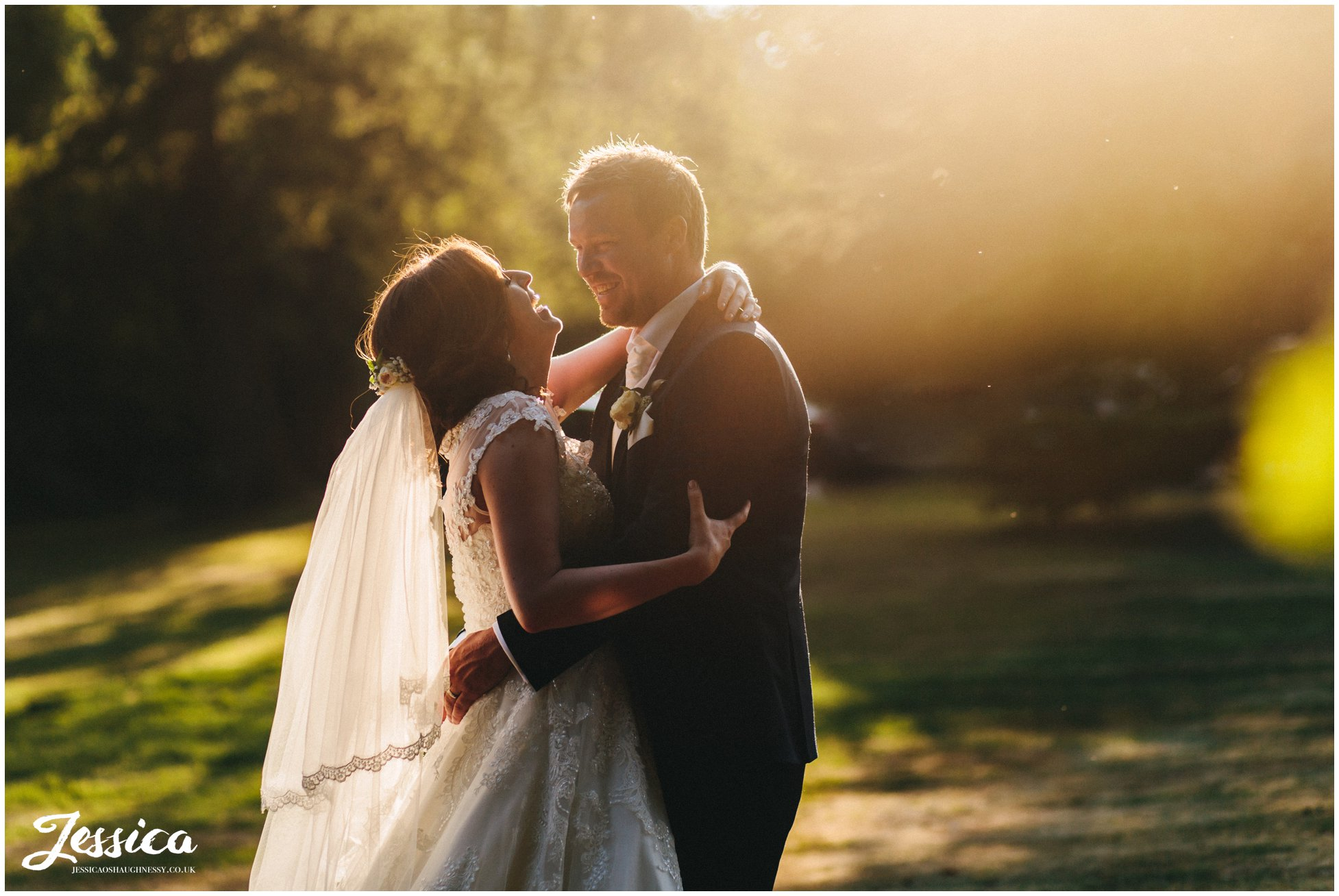 couple embrace in the evening sun outside their north west wedding venue, bartle hall