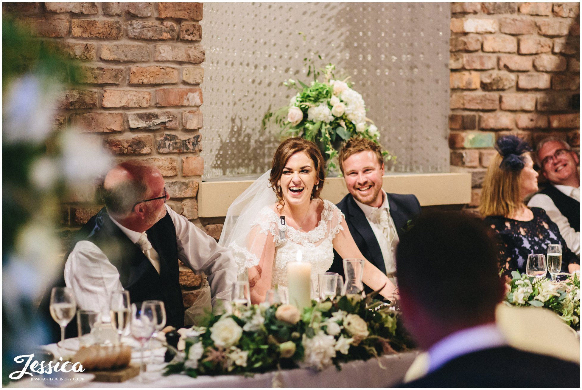 husband and wife laugh on the table table during their wedding speeches