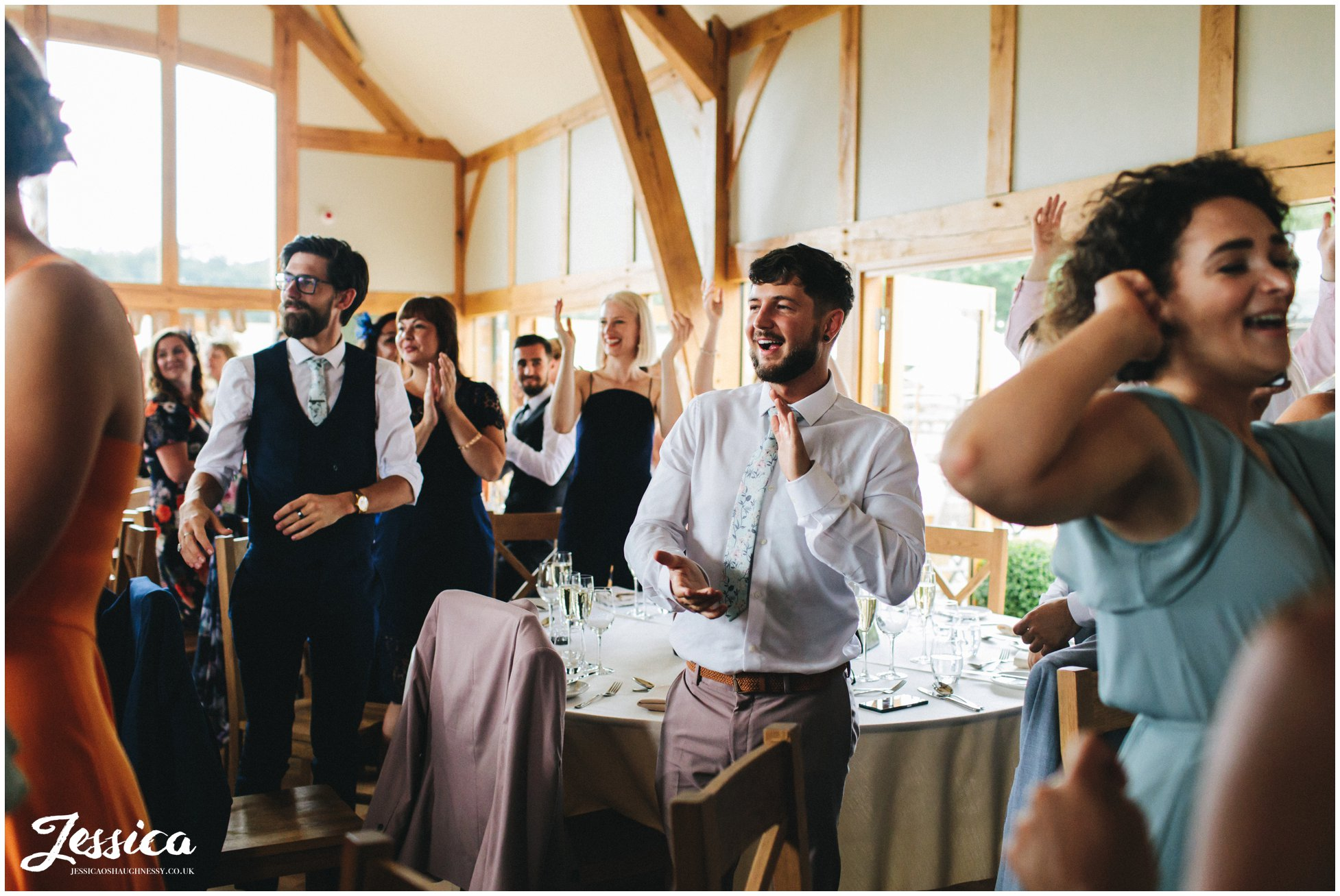 guests clap as they welcome in the new couple
