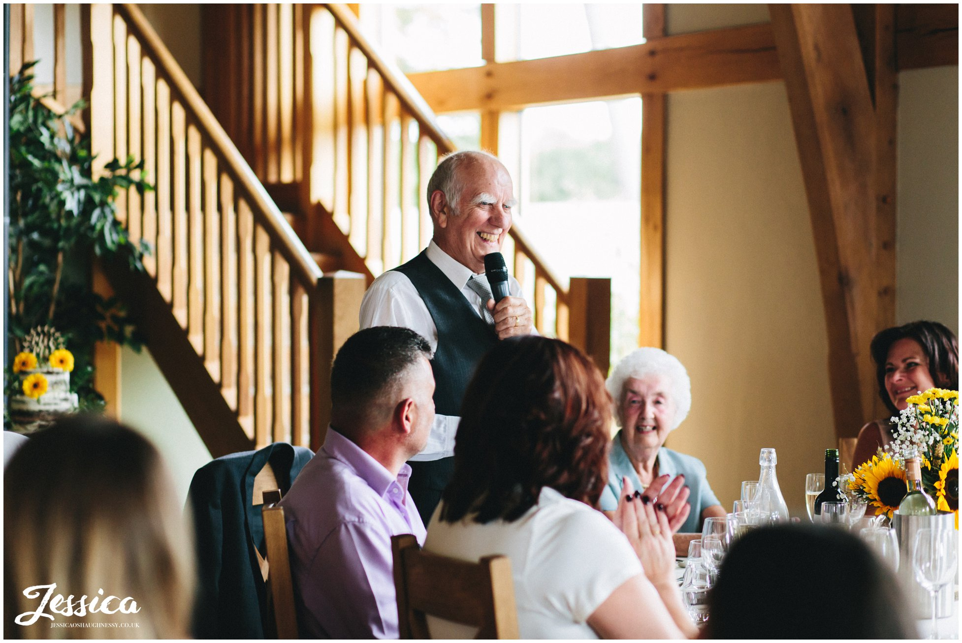 the brides grandfather makes a speech at the wedding reception