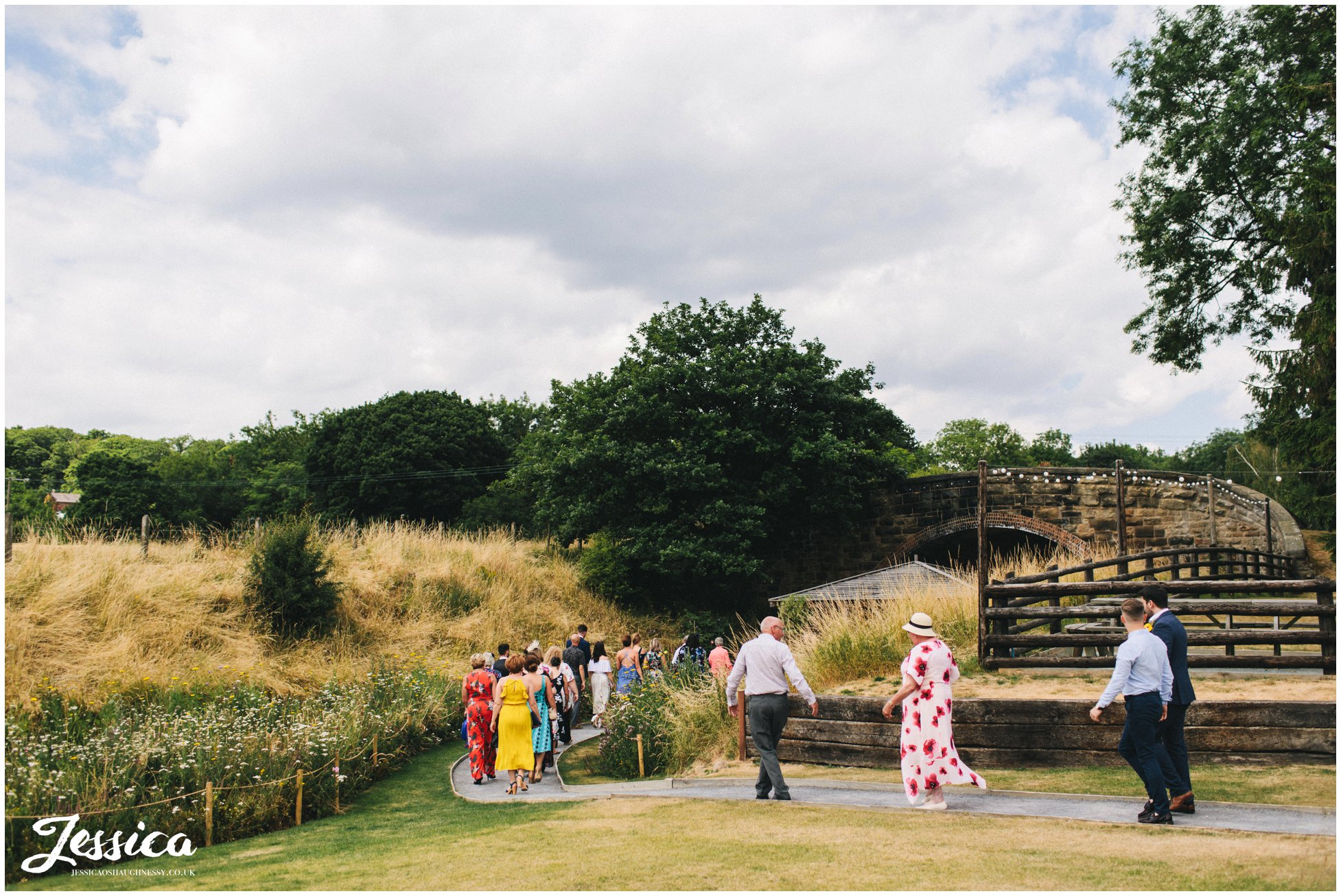 guests walk down the wildflower lined path to the bridge