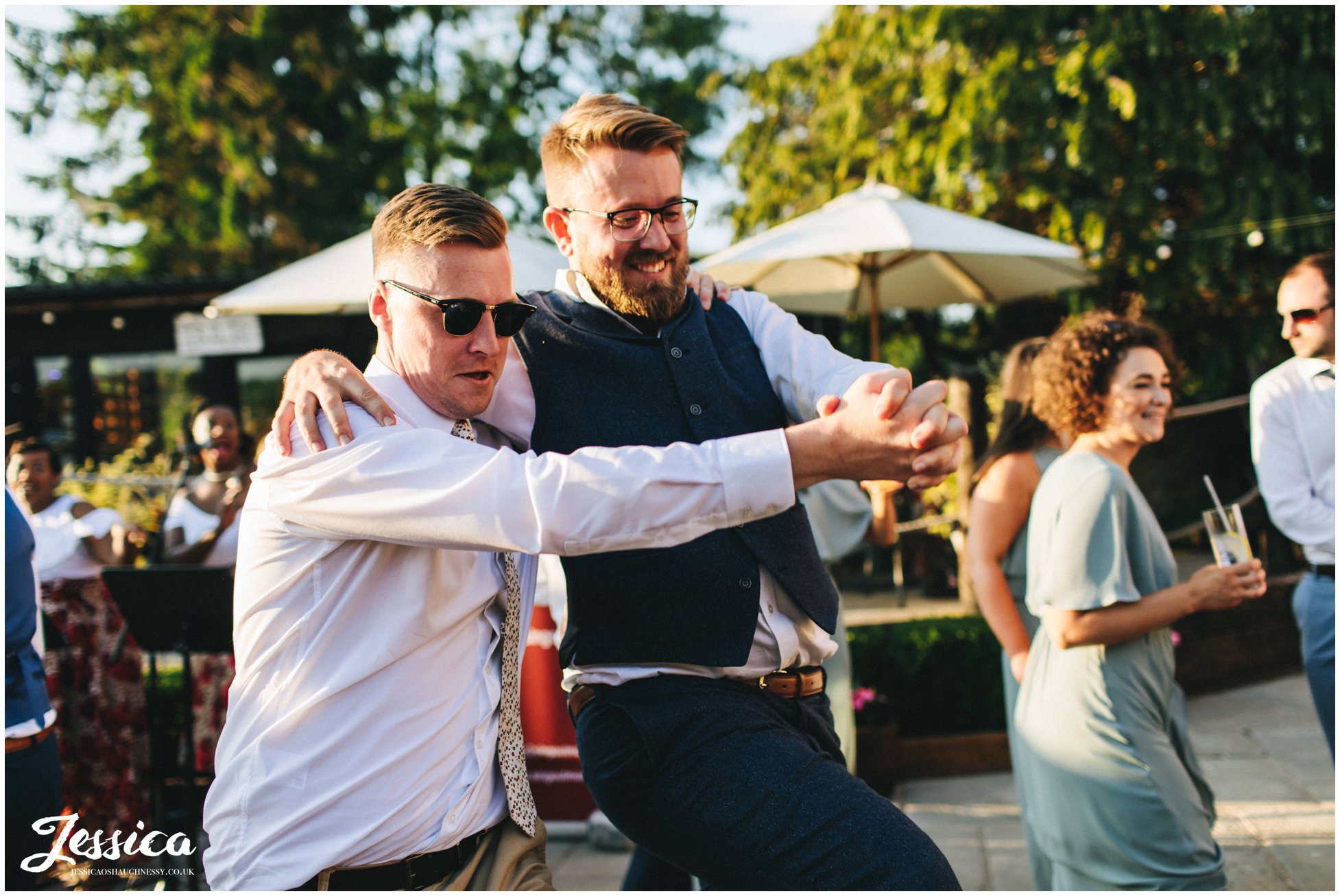 men dance together at the north wales wedding