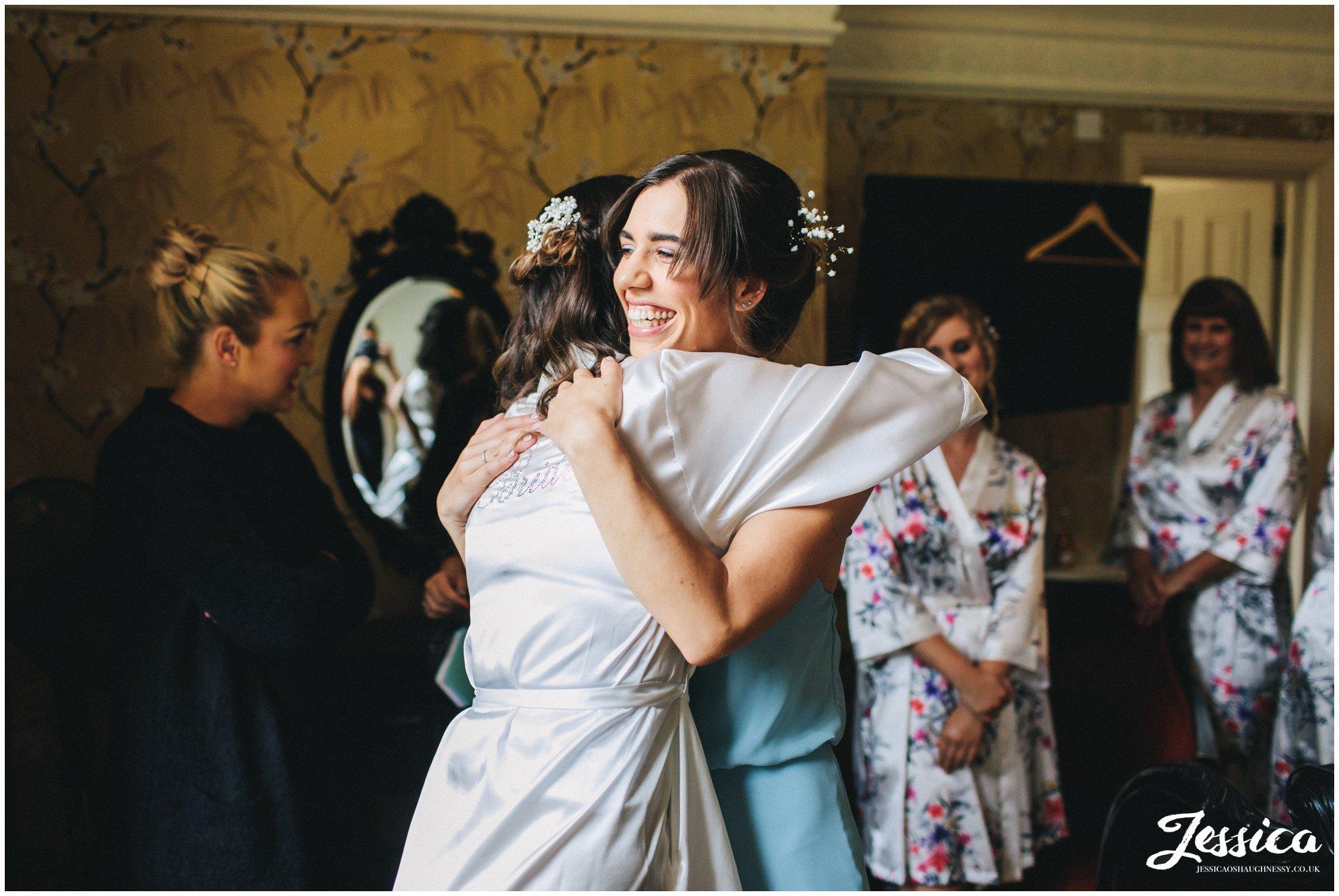 bride hugs her sister who is wearing her bridesmaid dress