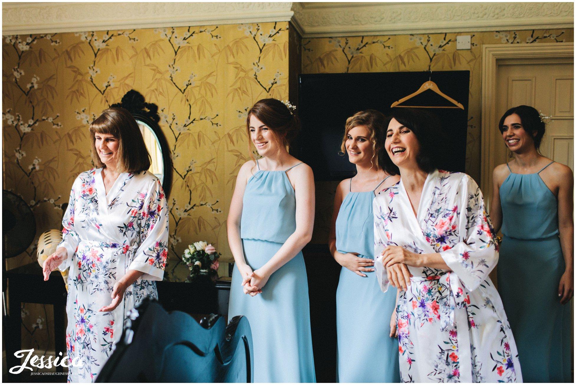 the bridesmaids admire their friend in her wedding dress