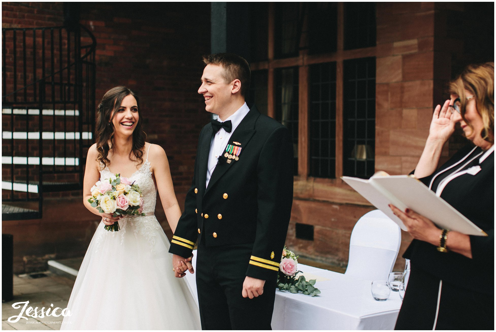 the couple hold hands laughing during their wedding ceremony