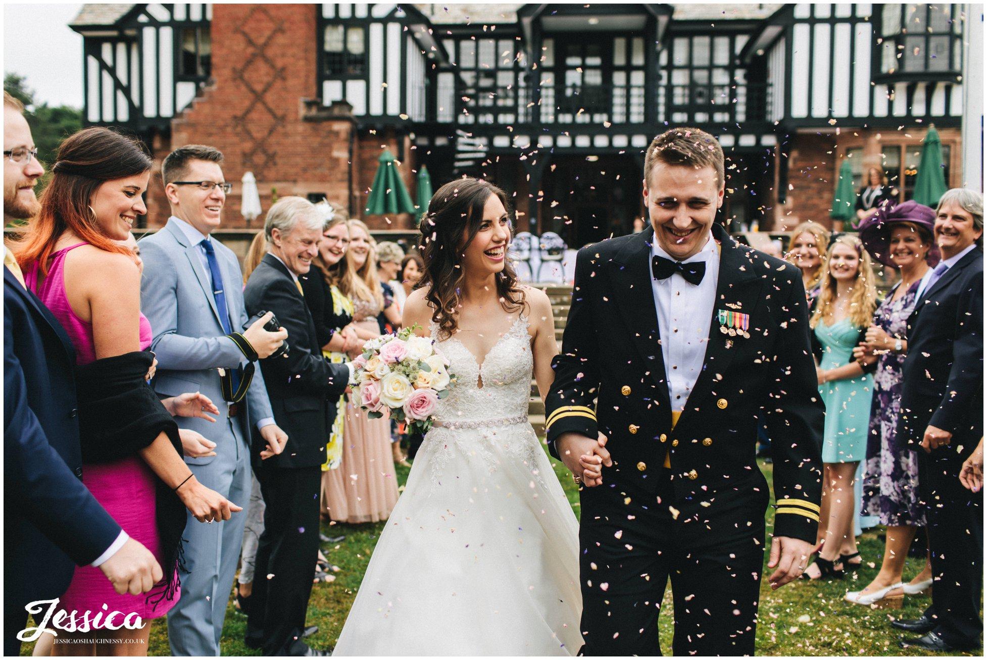 the bride and groom walk through confetti line