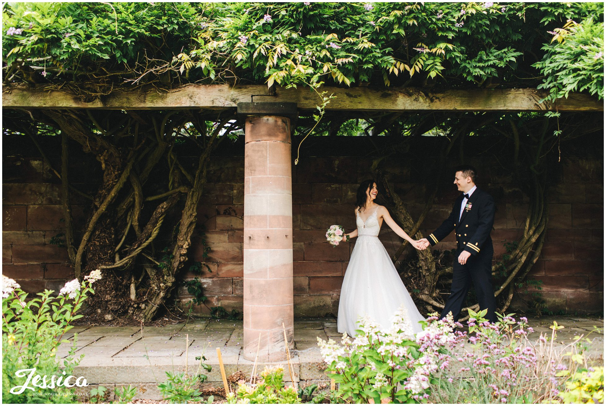 bride pulls her groom along under the wisteria path