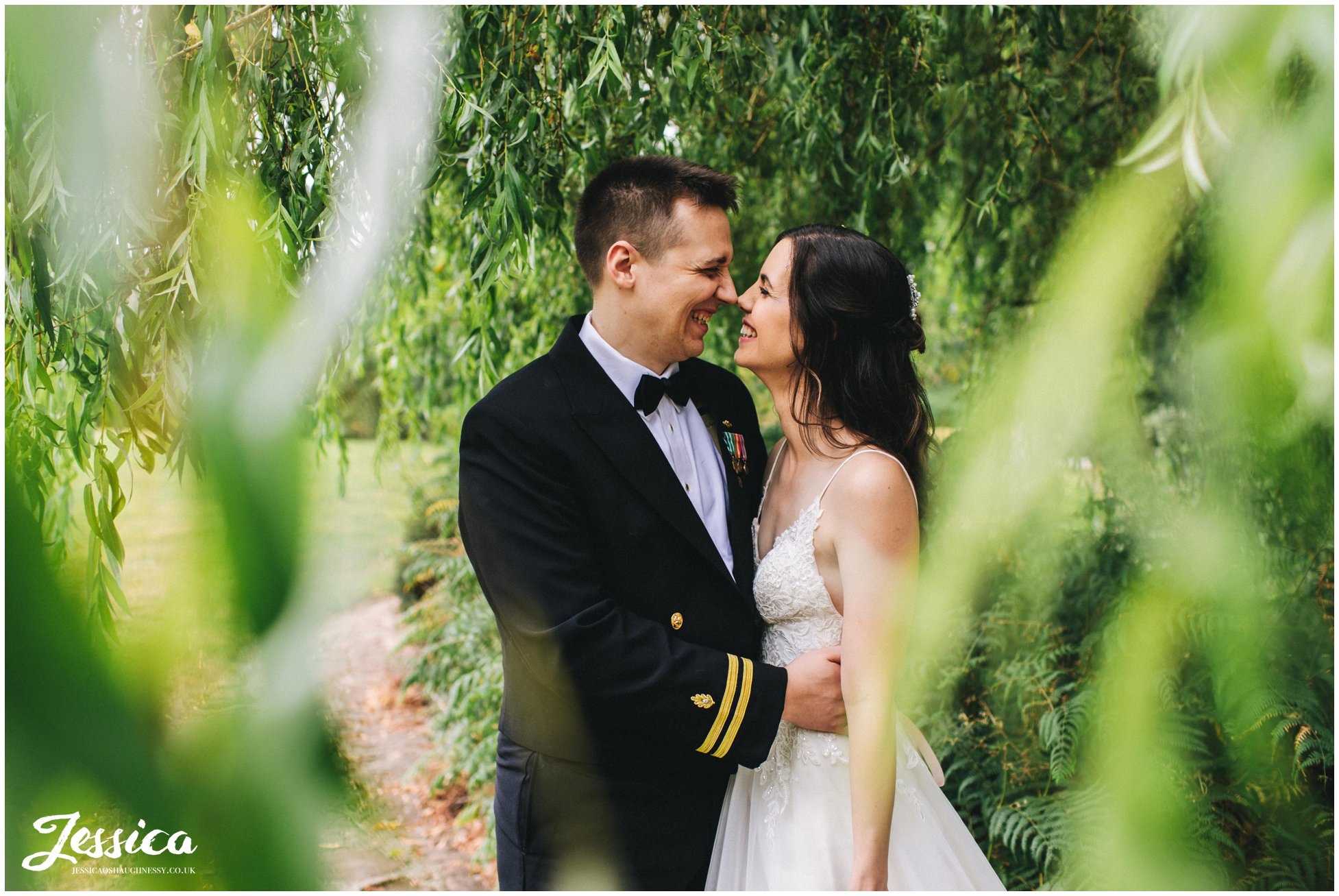 couple kiss under a willow tree at the cheshire wedding venue