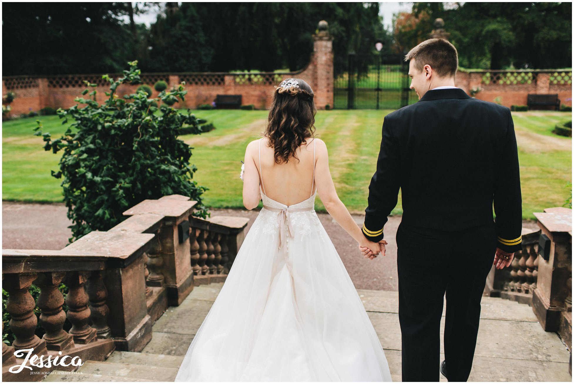 couple hold hands walking downstairs at their inglewood manor wedding