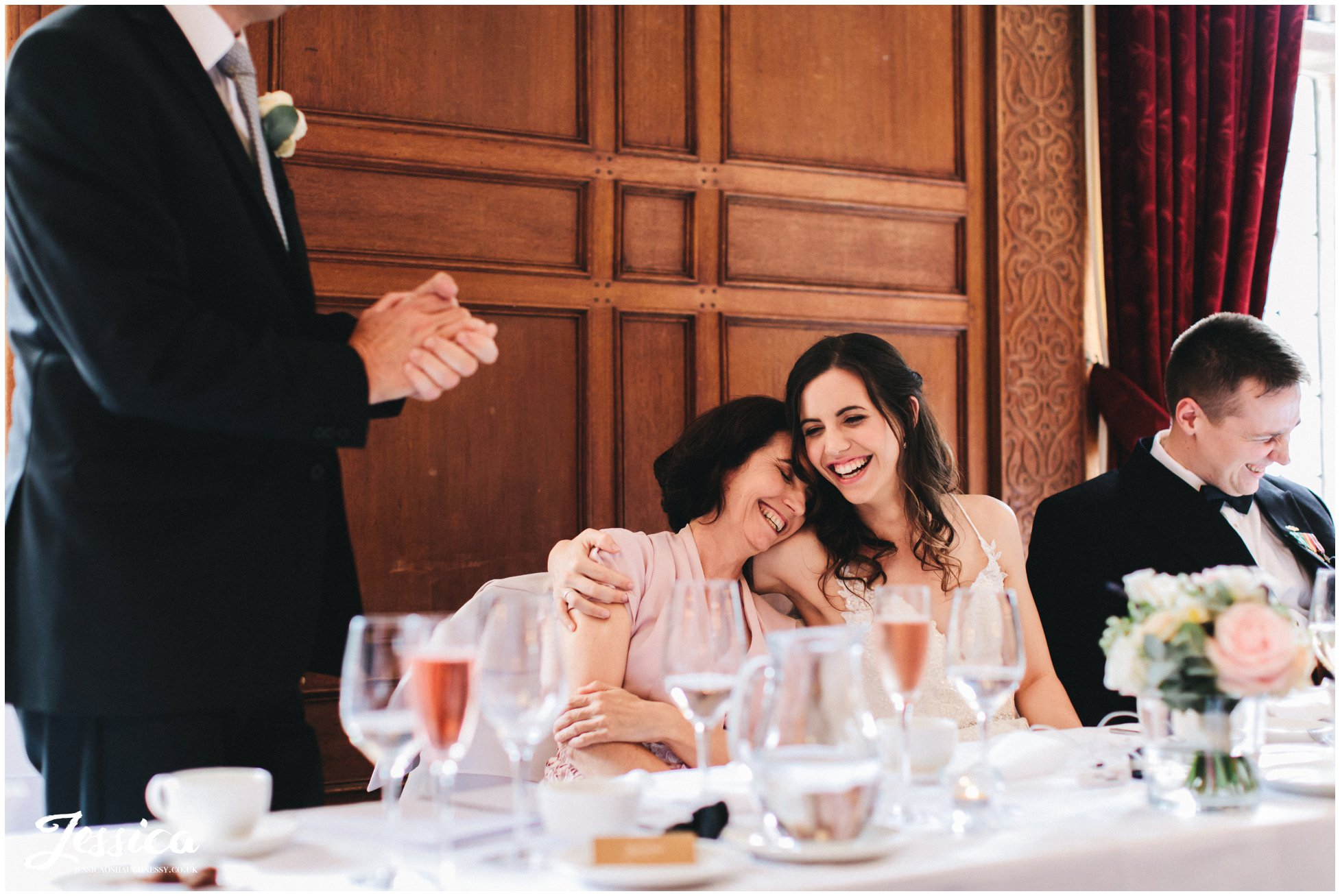 bride hugs her mother during father of the brides speech